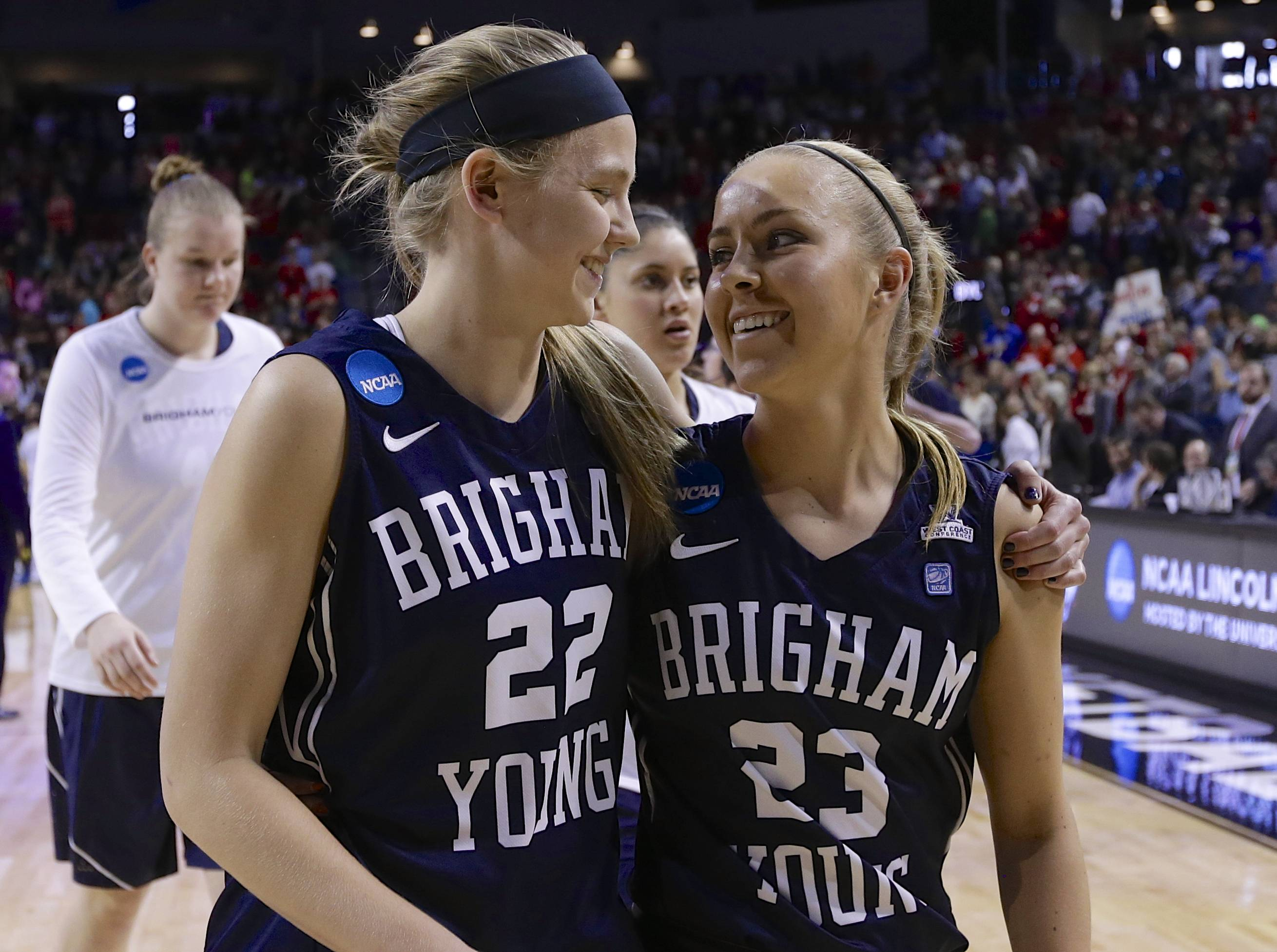 BYU's Kristine Fuller (22) and Makenzi Morrison (23) hug as they walk off the court after a 70-51 loss to Connecticut.