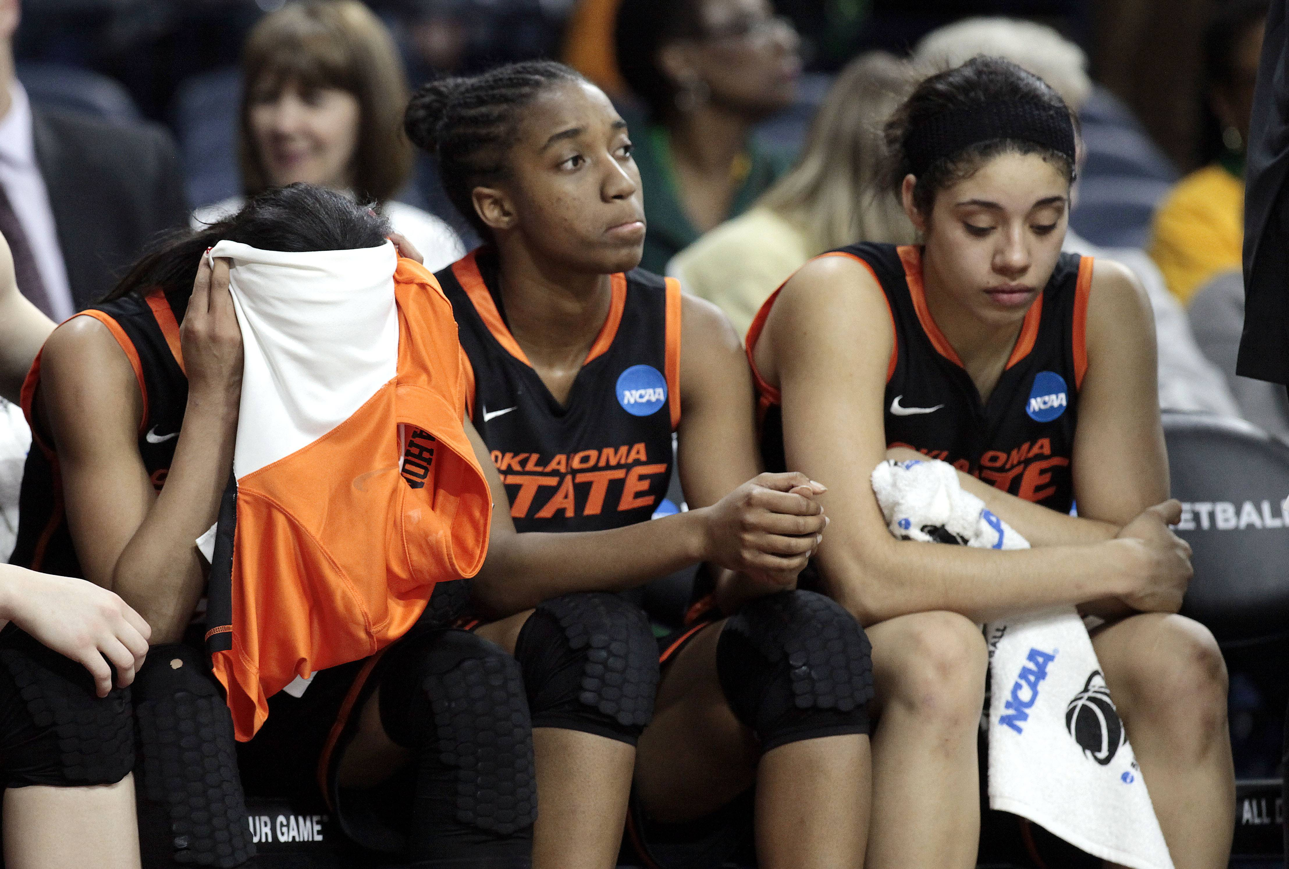 Oklahoma State players, from left, Tiffany Bias, Brittany Atkins and Brittney Martin sit on the bench during the closing moments against the Notre Dame in the second half.