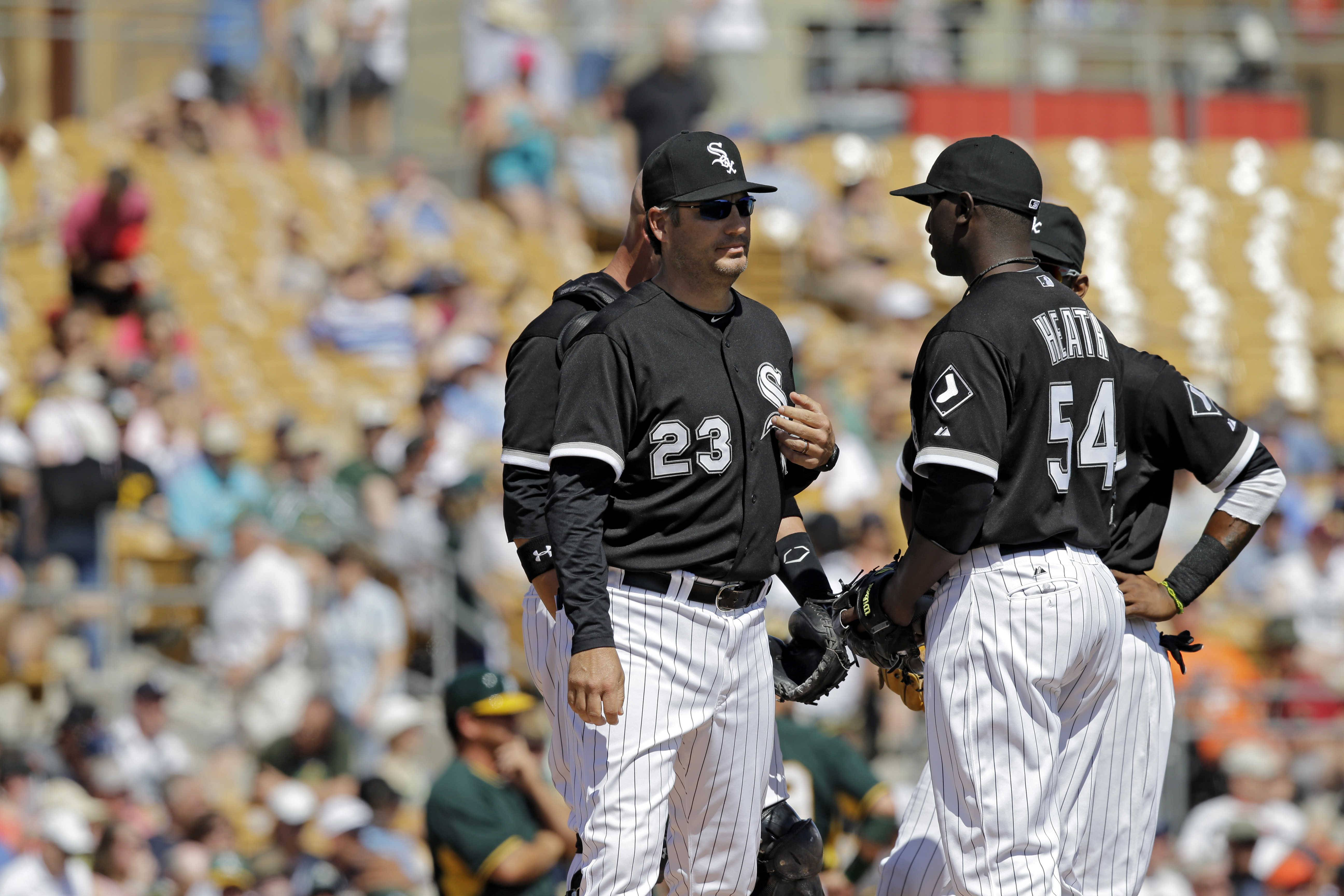Chicago White Sox manager Robin Ventura (23) talks to relief pitcher Deunte Heath (54) in a spring exhibition baseball game against the Oakland Athletics earlier this month in Glendale, Ariz. (AP Photo/Mark Duncan)