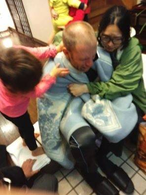 Mike Blodgett, who is from Batavia but lives in Japan, gets a little tender loving care from his wife, Ikuchan, and their daughter, Olivia. Blodgett went missing for six days while hiking on Mount Omine.
