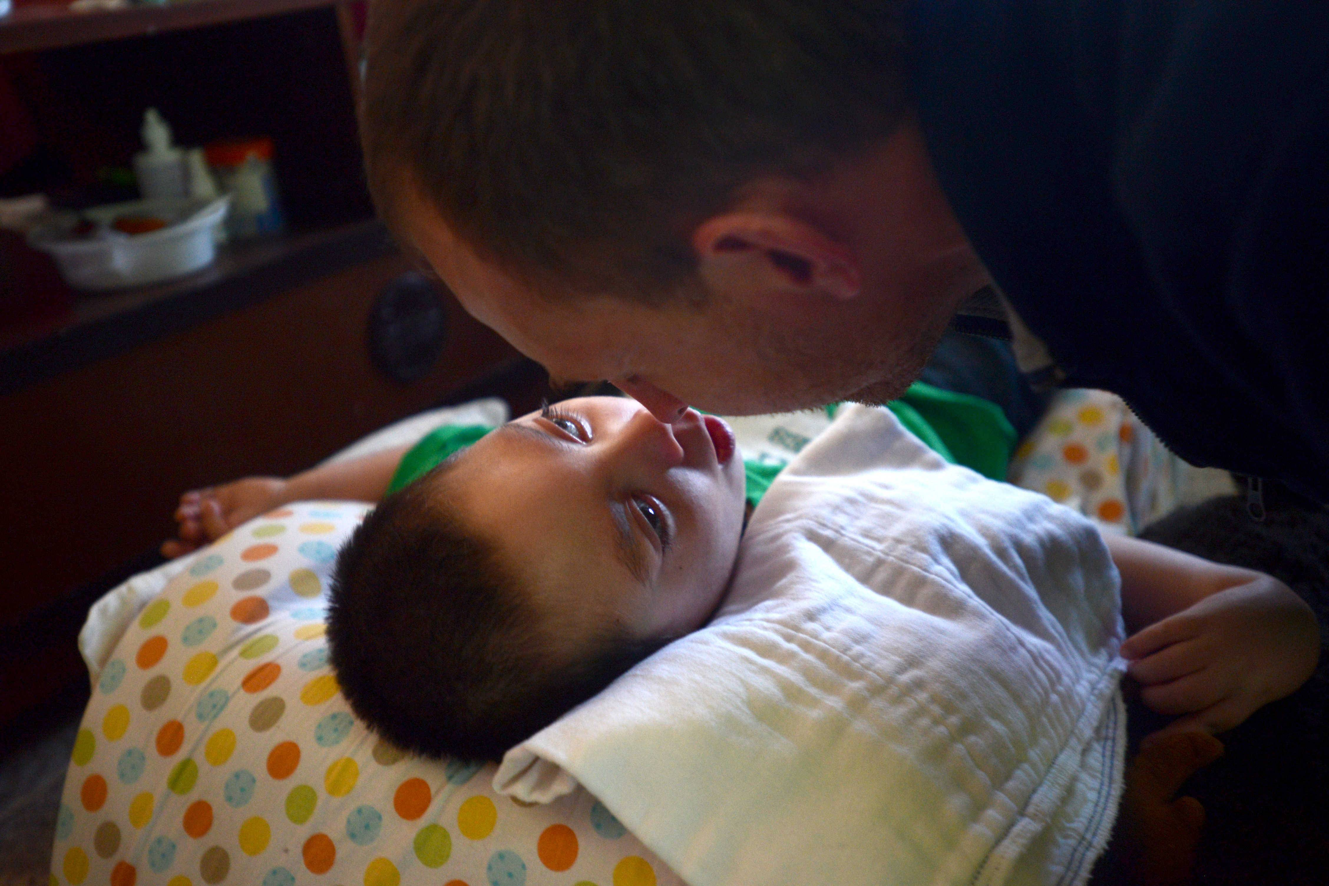 "Unable to move his limbs, speak or blink, 4-year-old James exchanges a ""nose bump"" with his father, Jeff Fulkerson. Stacy and Jeff Fulkerson of Schaumburg hope an April 6 fundraiser moves them closer to their dream of buying a special van to transport their son."