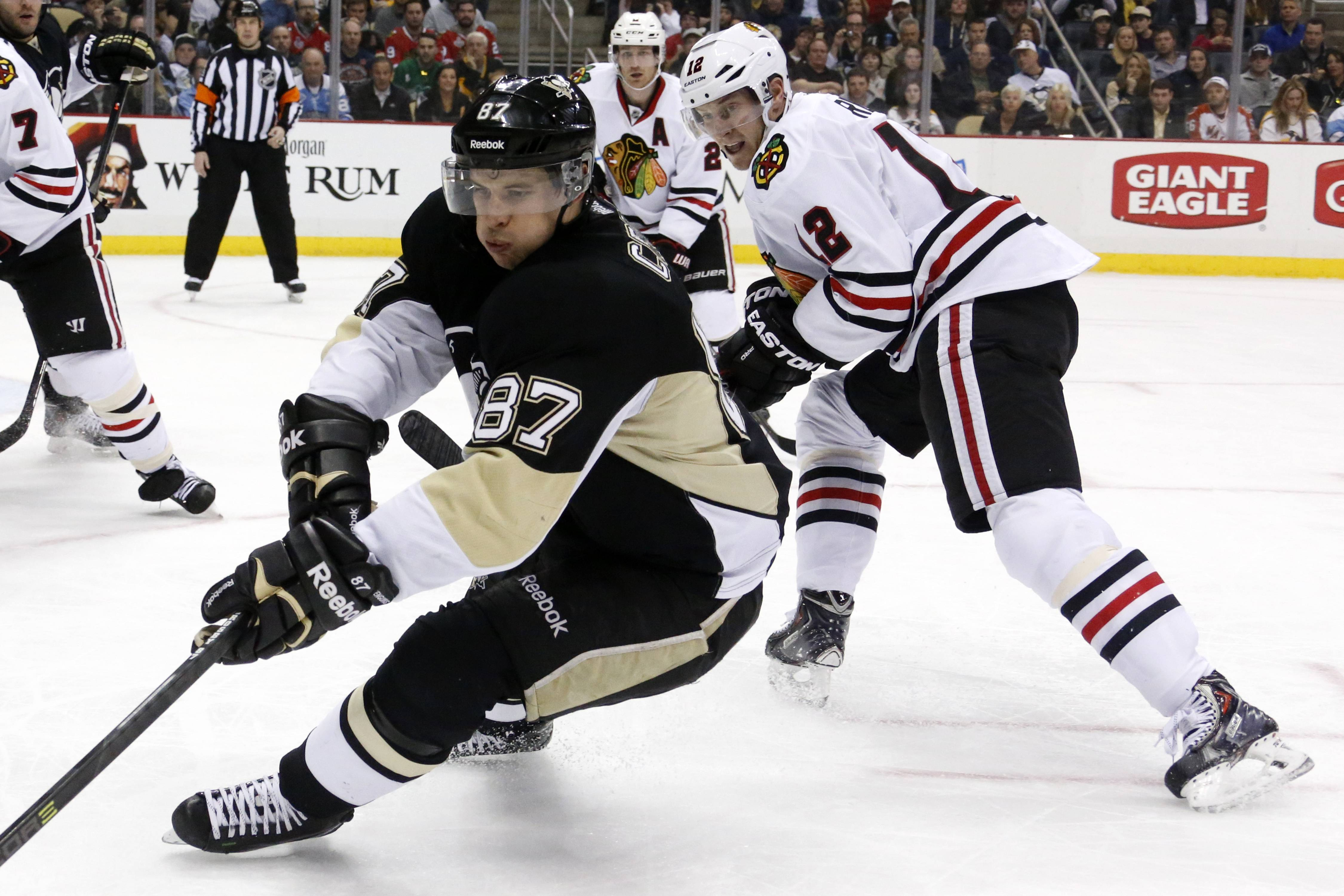 The Pittsburgh Penguins' Sidney Crosby (87) works the puck in the corner against Chicago Blackhawks center Peter Regin (12) in the second period of an NHL hockey game in Pittsburgh, Sunday, March 30, 2014. Crosby scored twice to lead the Penguins to a 4-1 win over the Blackhawks.