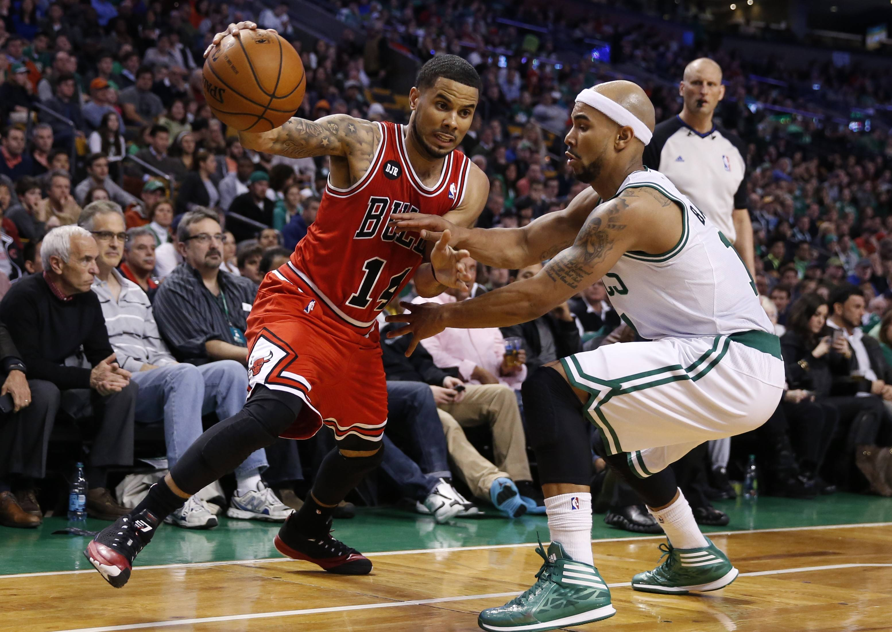 Chicago Bulls' D.J. Augustin (14) drives past Boston Celtics' Jerryd Bayless in the second quarter of an NBA basketball game in Boston, Sunday, March 30, 2014.