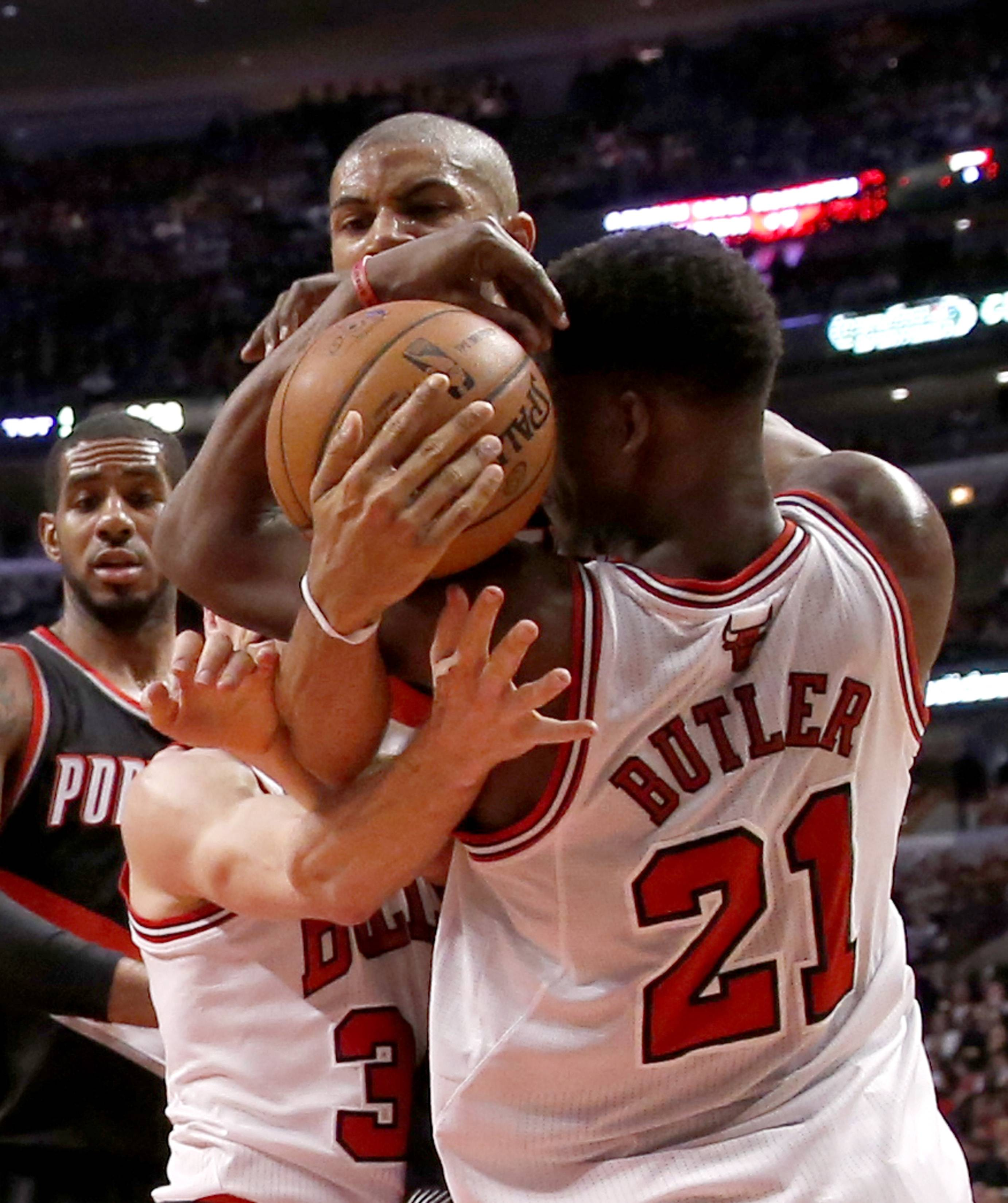Portland's Nicolas Batum, top, battles Bulls forward Mike Dunleavy and Jimmy Butler for a rebound during the second half Friday night. The Trail Blazers won 91-74.