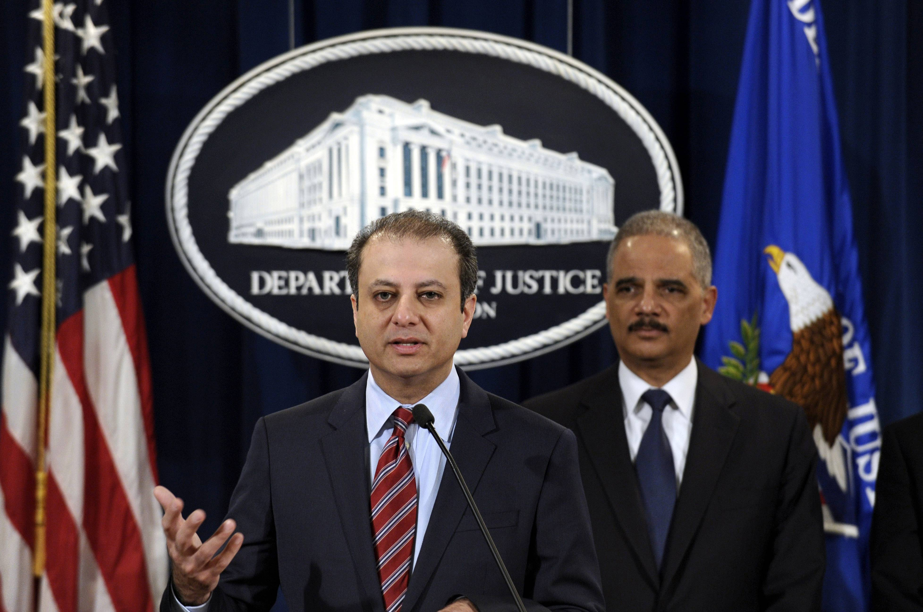 Attorney General Eric Holder, right, listens as U.S. Attorney for the Second District Preet Bharara talks about the $1.2 billion settlement with Toyota over its disclosure of safety problems during a news conference at the Justice Department in Washington.