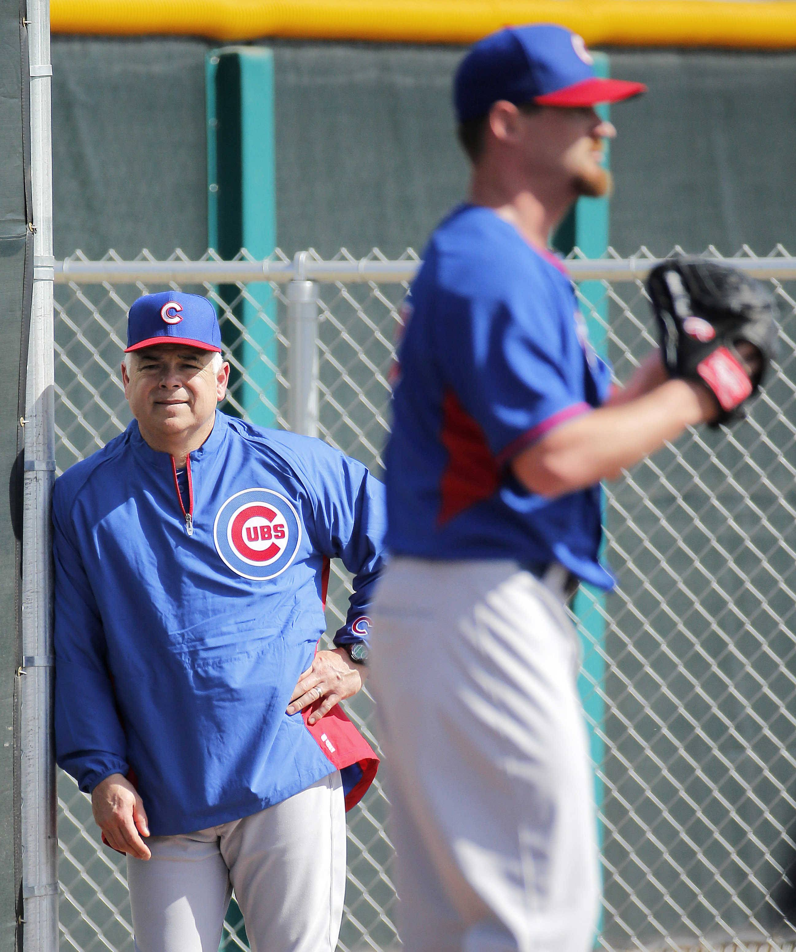 Chicago Cubs manager Rick Renteria, left, watches pitcher Travis Wood throw during the team's first spring training baseball practice in February in Mesa, Ariz.