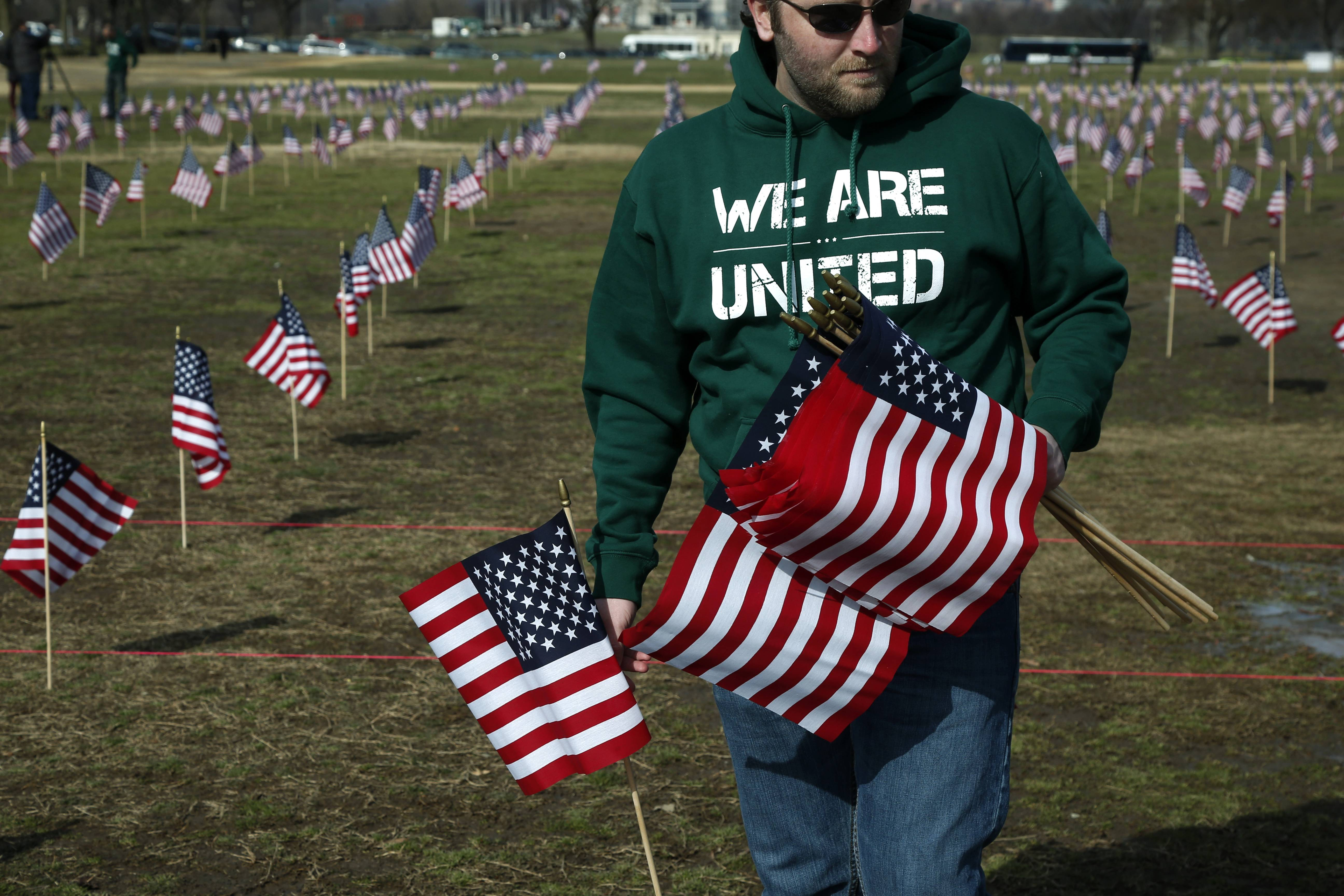 Army veteran Michael Blazer from Lebanon, Tenn., now with Iraq and Afghanistan Veterans of America, joins others to place 1,892 flags representing veteran and service members who have died by suicide to date in 2014, Thursday on the National Mall in Washington.