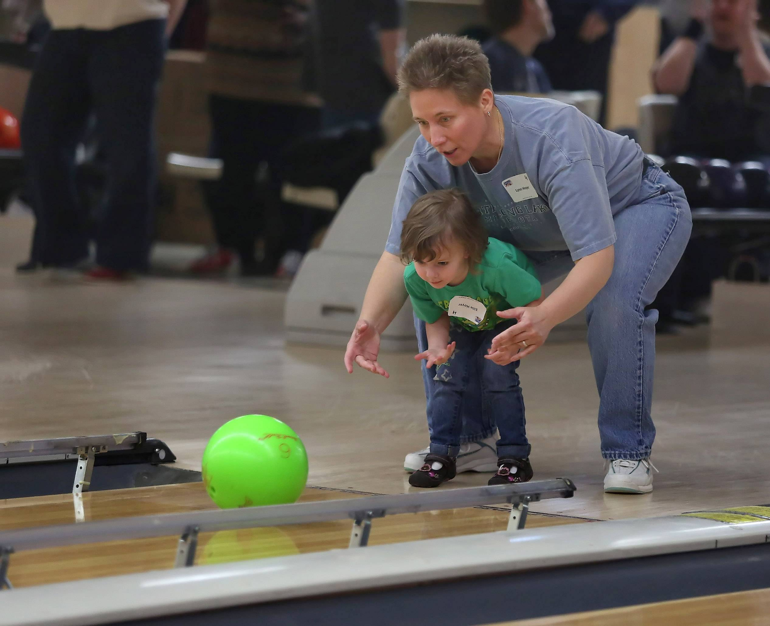 "Lynn Hoyer of Crystal Lake helps her daughter, Ellie, 3, bowl Sunday during the ""Pits For Patriots Stars and Strikes Fundraiser"" at Hoffman Lanes in Hoffman Estates. The event featured bowling, raffles and silent auctions and a bake sale to raise money to rescue pit bulls and train them for service work."