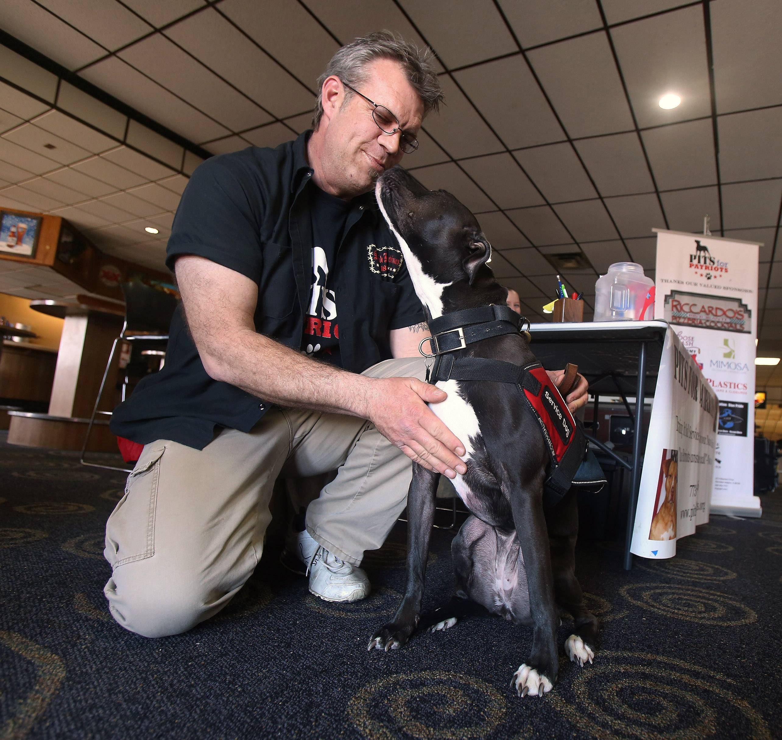 "Greg Yearwood of Bensenville receives a kiss from Mira, a rescued pit bull, during the ""Pits For Patriots Stars and Strikes Fundraiser"" Sunday at Hoffman Lanes in Hoffman Estates. The event featured bowling, raffles and silent auctions and a bake sale to raise money to rescue pit bulls and train them for service work."