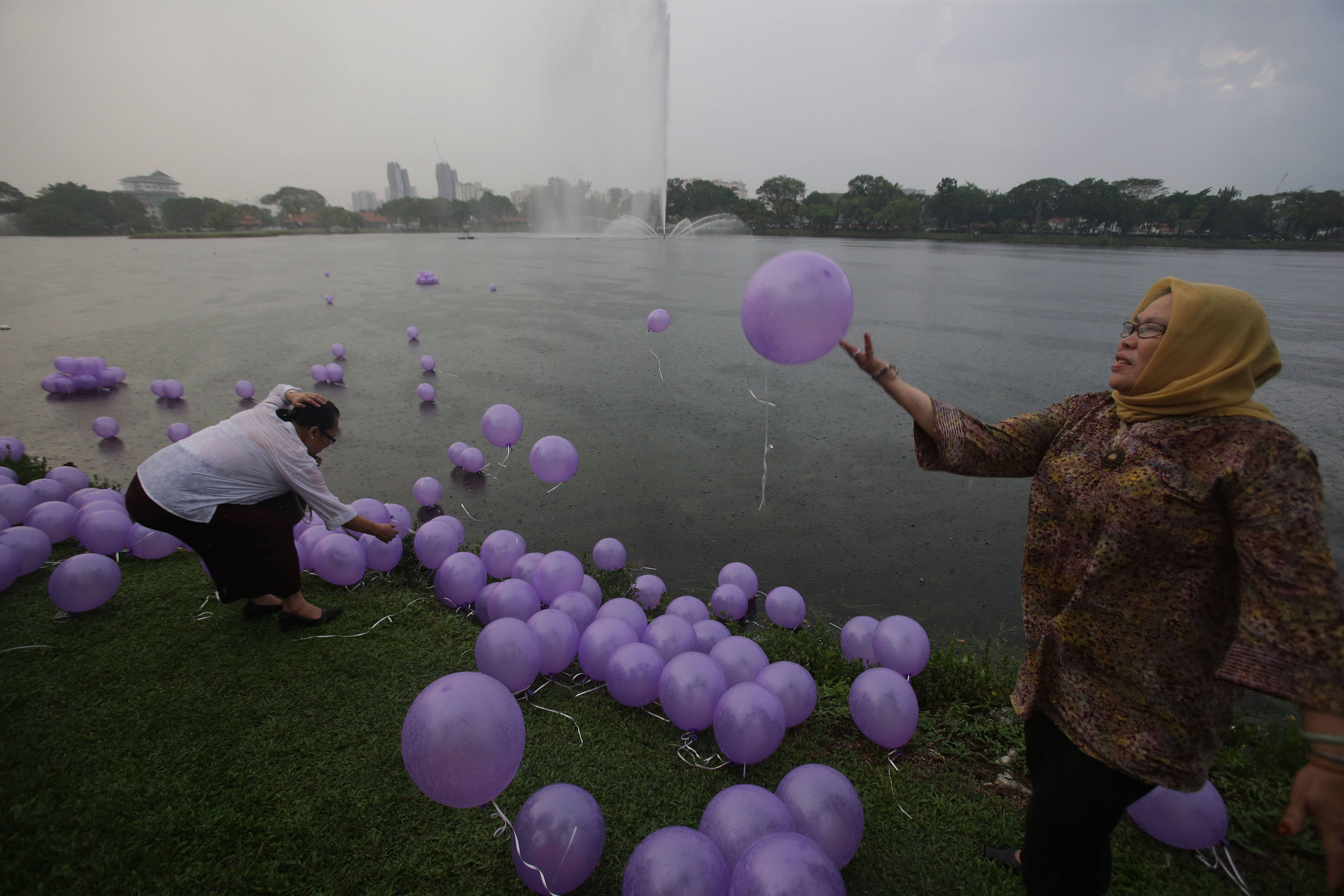 Women release balloons to symbolize their prayers for the 239 passengers on board the missing Malaysia Airlines flight MH370, at a park at Kuala Lumpur, Malaysia, Sunday. A new batch of relatives from China has arrived today to seek answers of what happened to their loved one on board flight MH370.
