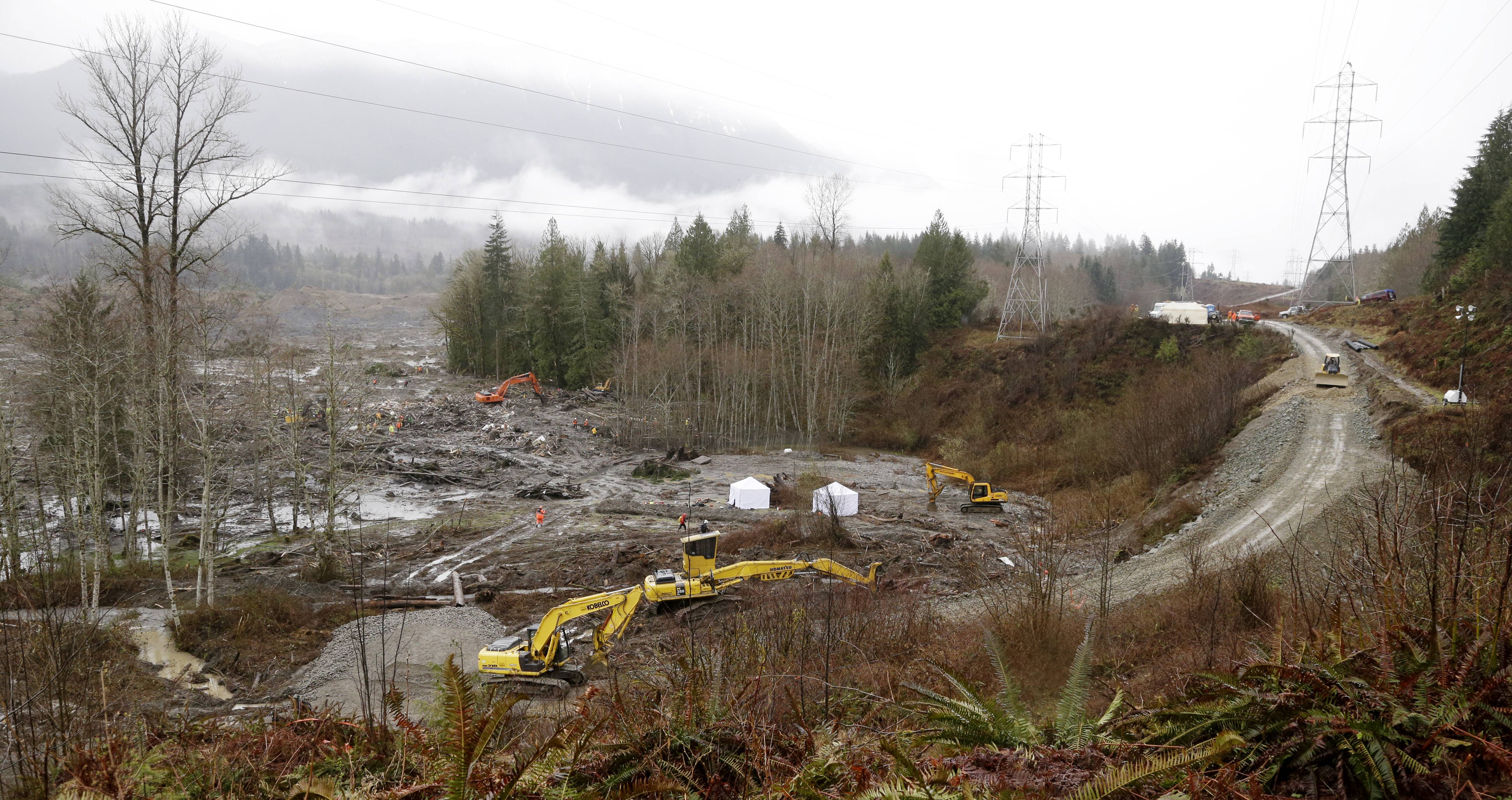 A road continues to be built at right to connect the two sides of the scene of a deadly mudslide to allow searchers though in Oso, Wash. Besides the more than two dozen bodies already found, many more people could be buried in the debris pile left from the mudslide one week ago.
