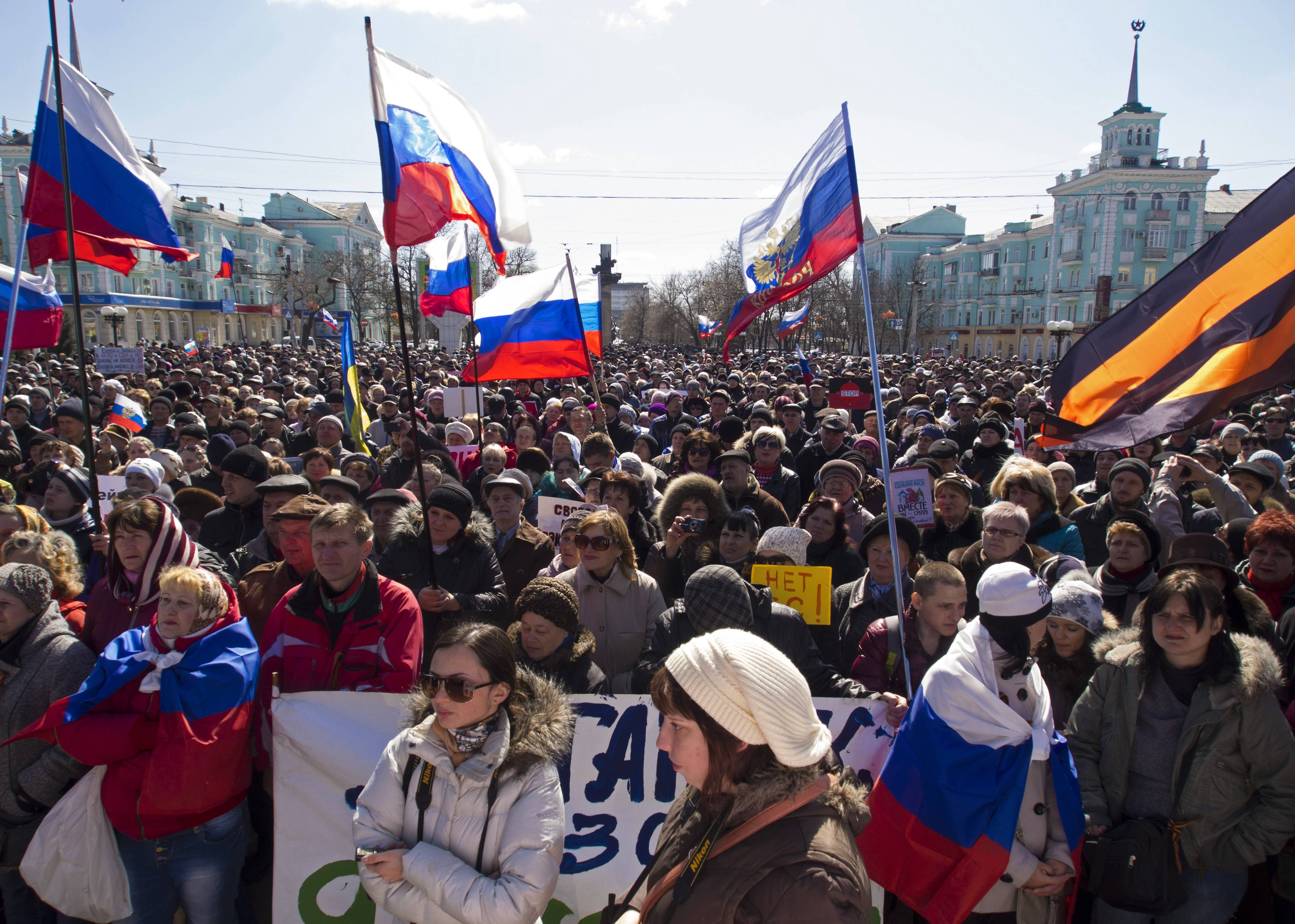 Pro-Russian demonstrators hold Russian national flags during an anti-government rally in Luhansk, Ukraine, Sunday. As Ukraine moves quickly to build up its governance, it still casts an uneasy eye toward Russia, fearing a possible troop invasion into eastern Ukraine.