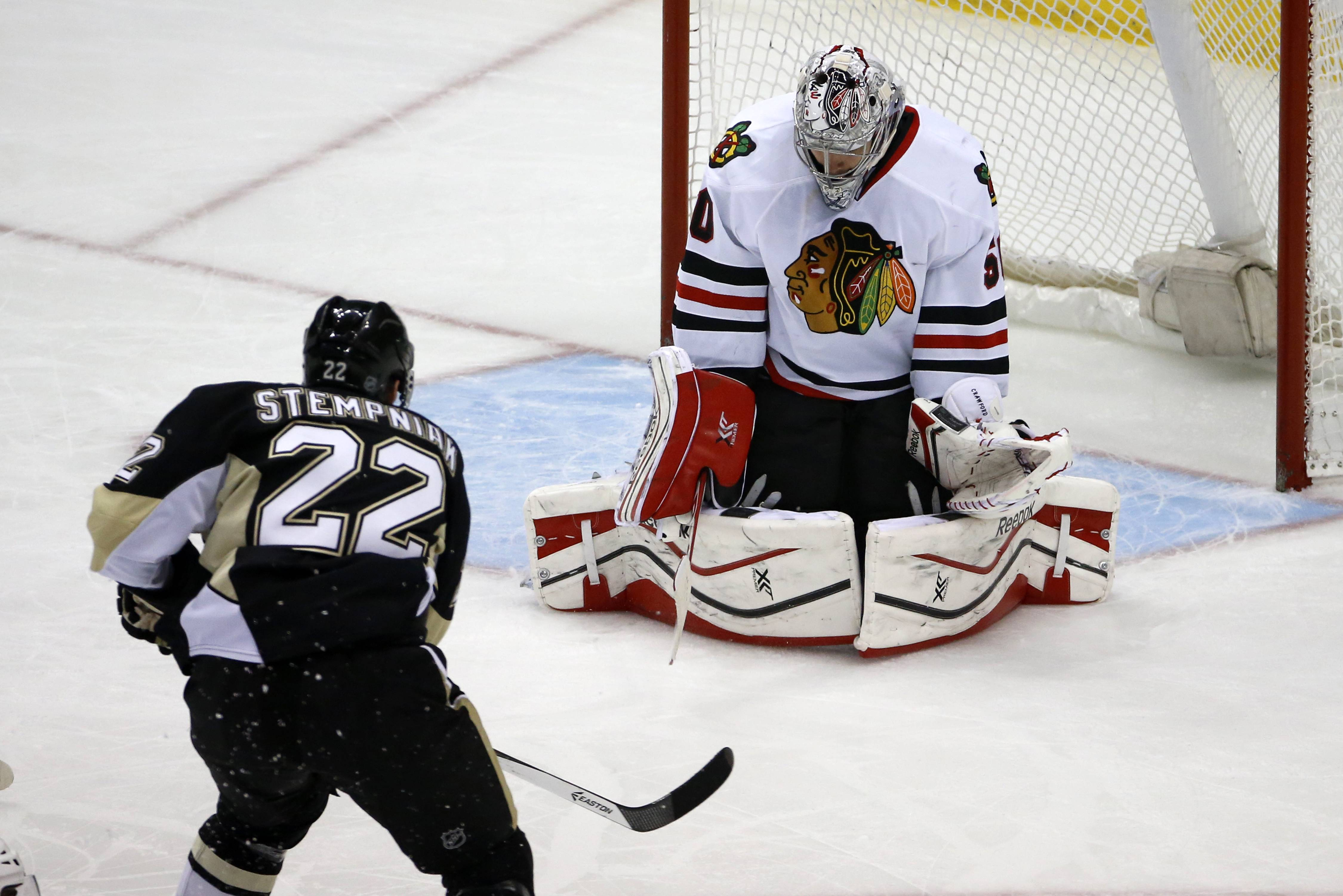 The Penguins' Lee Stempniak puts the puck behind Hawks goalie Corey Crawford in the first period Sunday night.