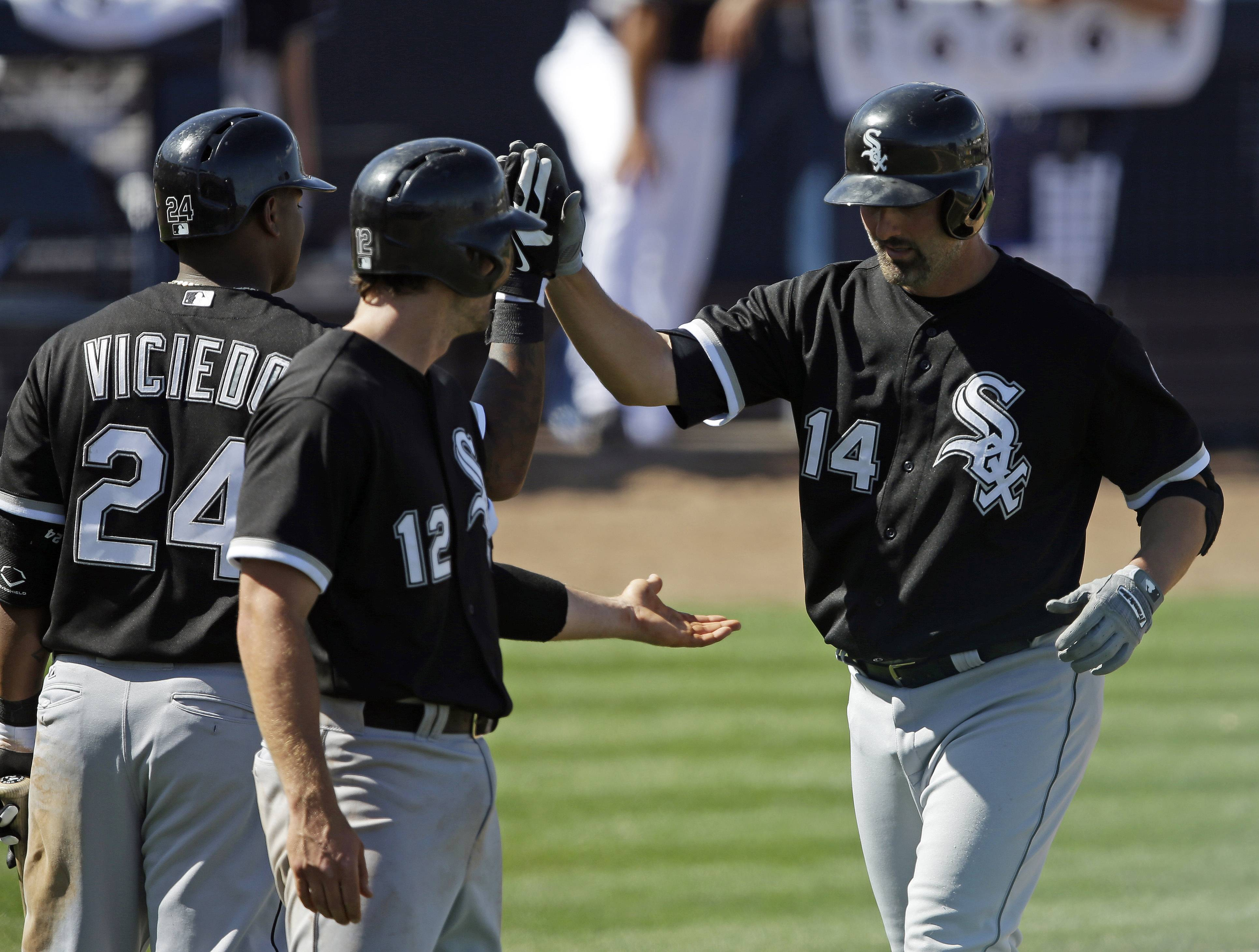 The White Sox' Paul Konerko (14) is congratulated by Conor Gillaspie (12) and Dayan Viciedo (24) after hitting a 2-run home run against the Seattle Mariners last week in Arizona.