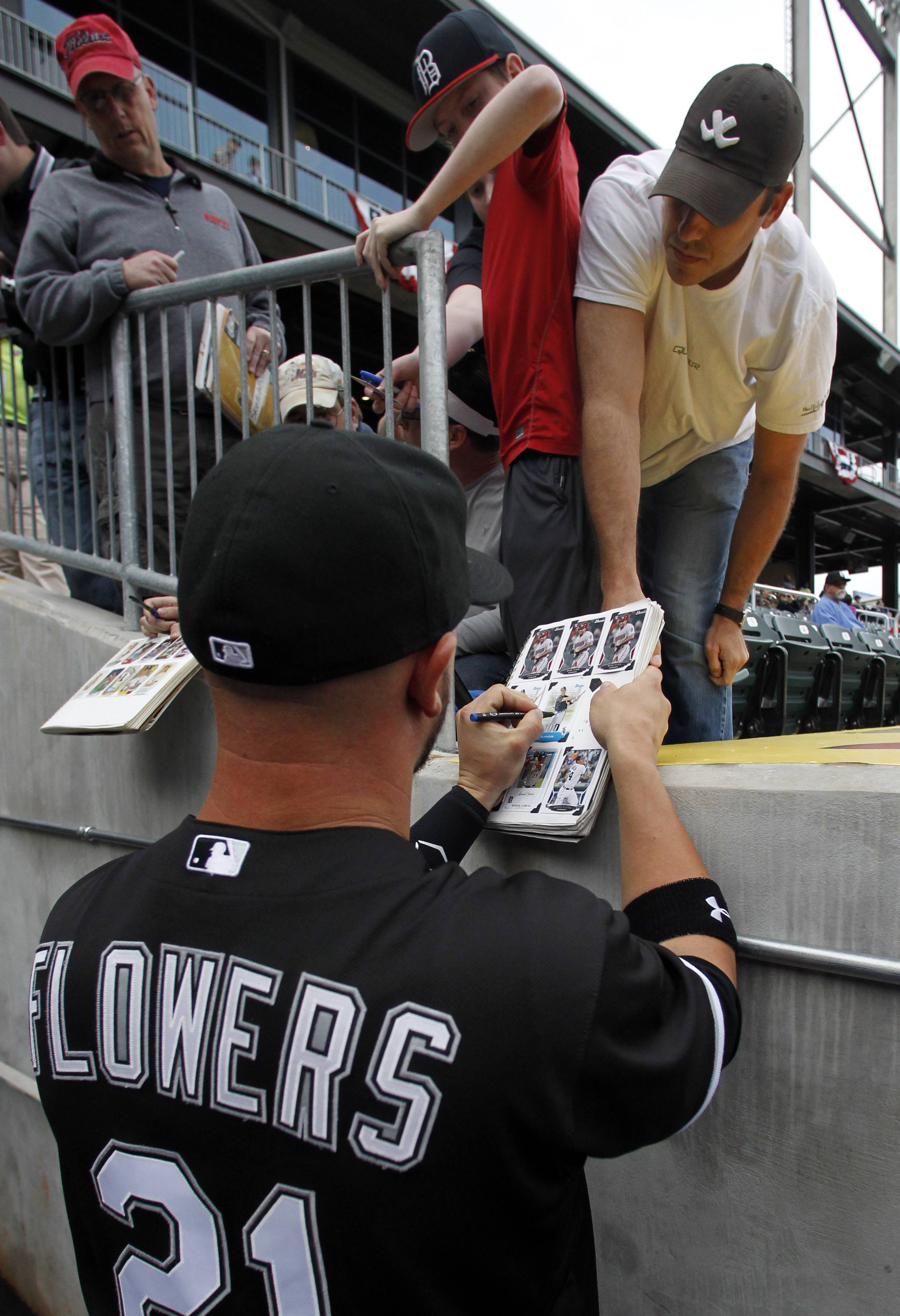 White Sox catcher Tyler Flowers autographs a photo for a fan.