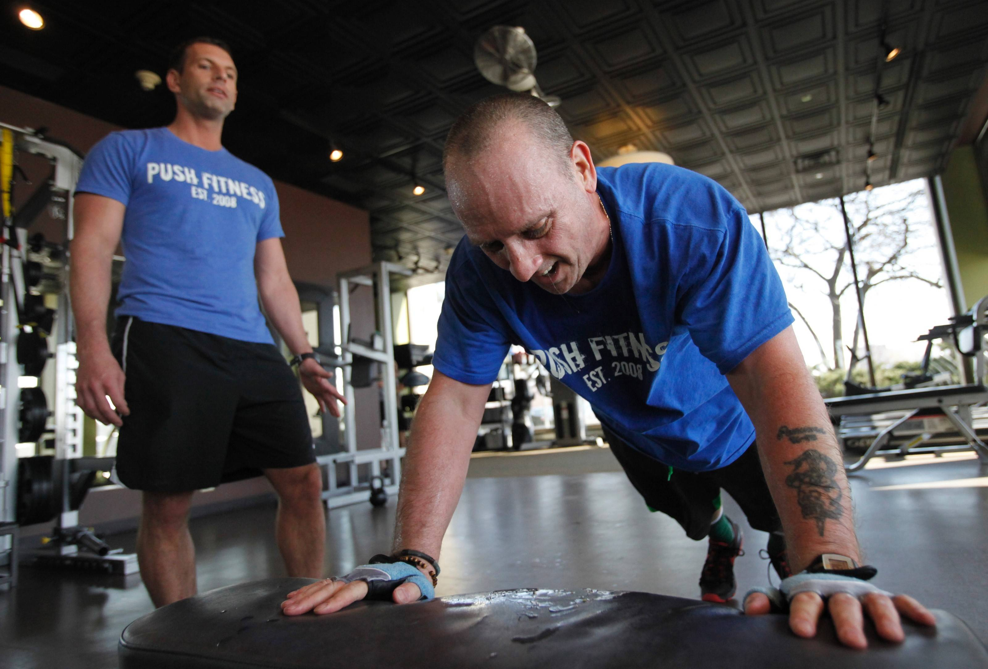 Trainer Steve Amsden makes sure Fittest Loser Tim Lange works hard in the gym.