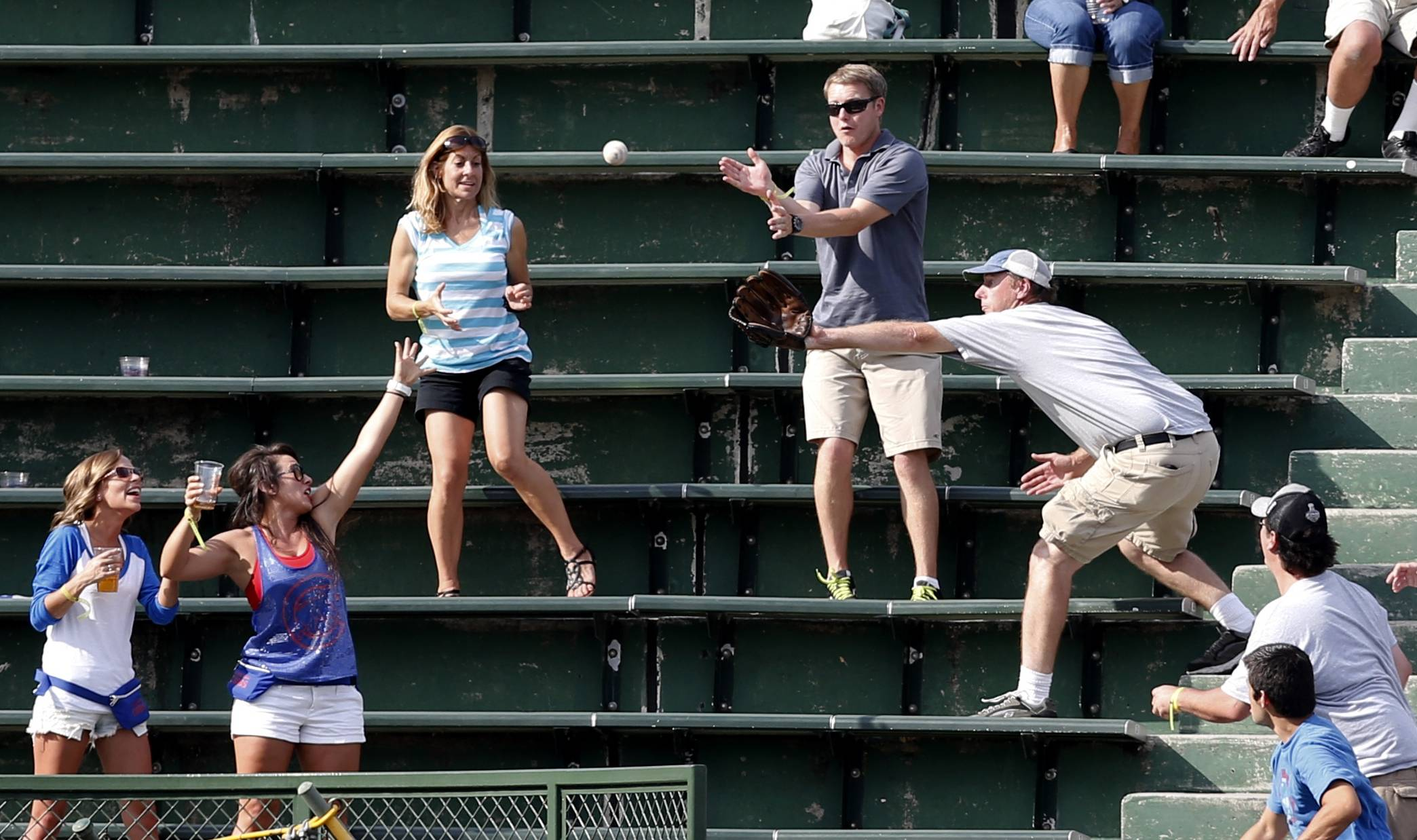 Baseball fans in Wrigley Field's left field bleachers scramble for a batted ball during a Chicago Cubs baseball game in Chicago. Wrigley was the first ballpark where fans could keep foul balls.