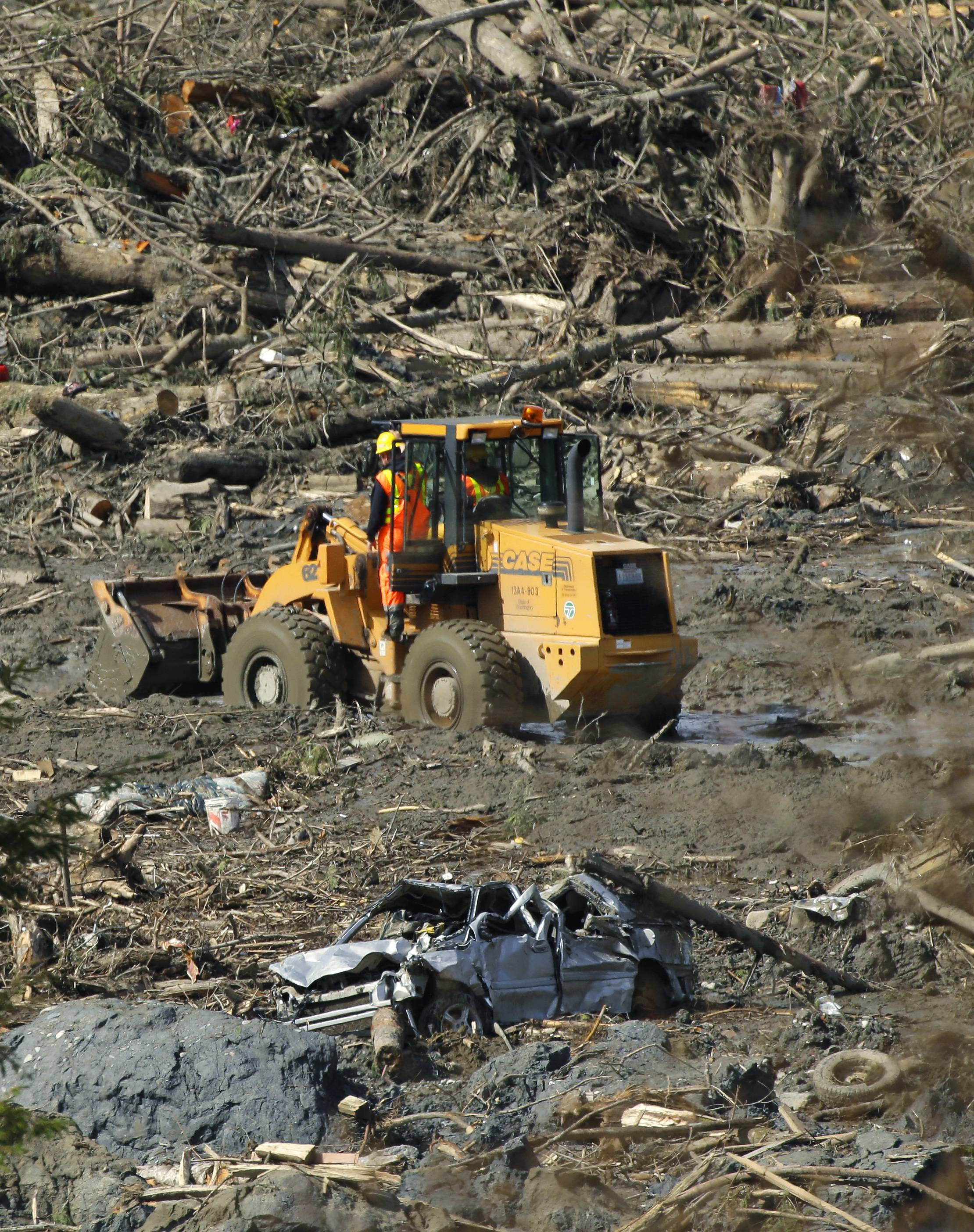 ASSOCIATED PRESS A front-end loader is driven past a wrecked car Monday near Darrington, Wash., in the debris field of the massive mudslide that hit the nearby community of Oso, Wash.