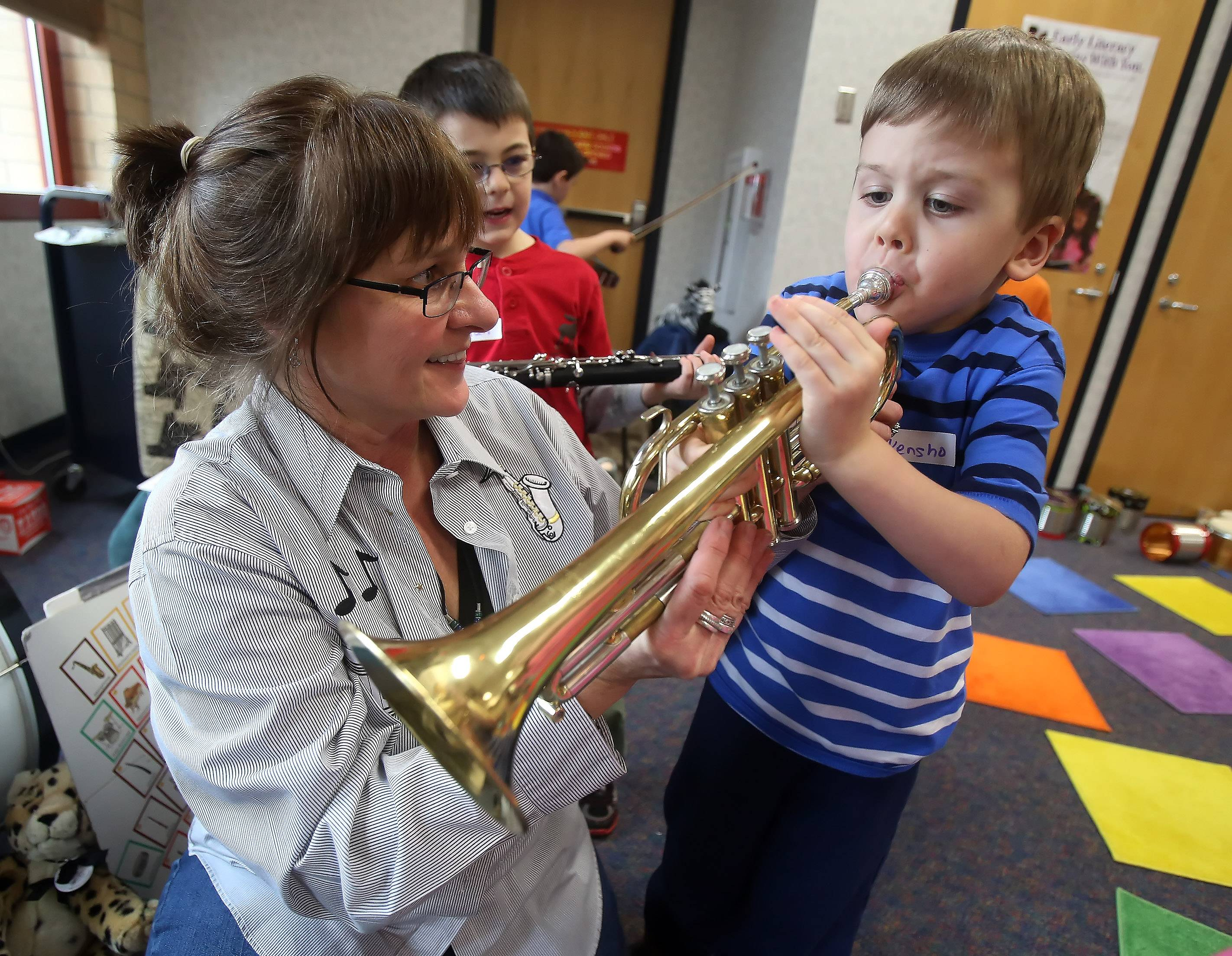 "Children's music instructor Susan Nierman, of Mundelein, helped Kensho Beasley, 5, also of Mundelein, play a trumpet during ""Ms. Sue's Musical Petting Zoo!"" program Thursday at the Fremont Public Library in Mundelein. Nierman introduced young children to a variety of musical instruments."