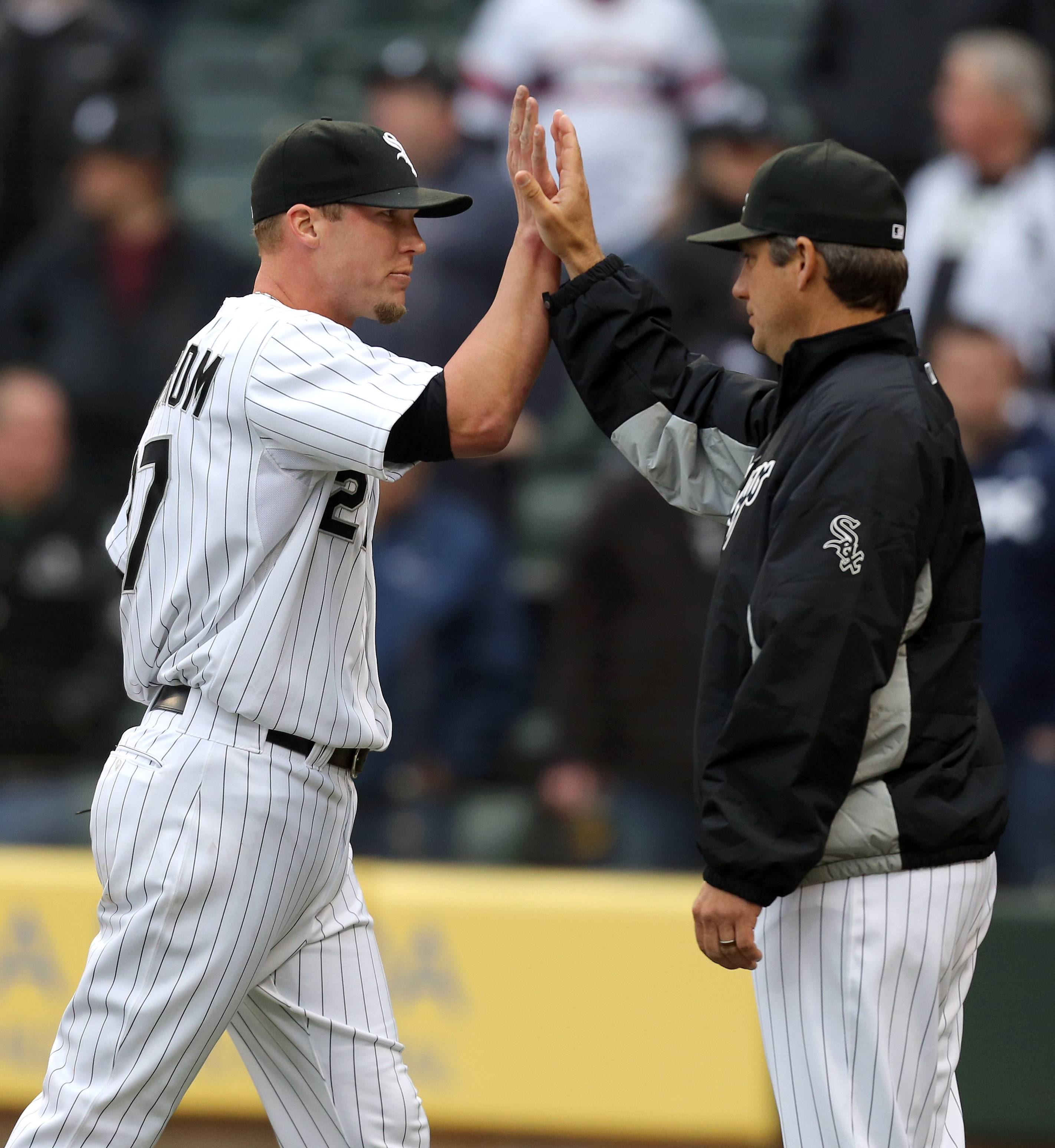 White Sox relief pitcher Matt Lindstrom, left, high fives Chicago White Sox manager Robin Ventura after getting the save in their 5-3 win during the White Sox home opener against the Minnesota twins Monday at US Cellular Field.