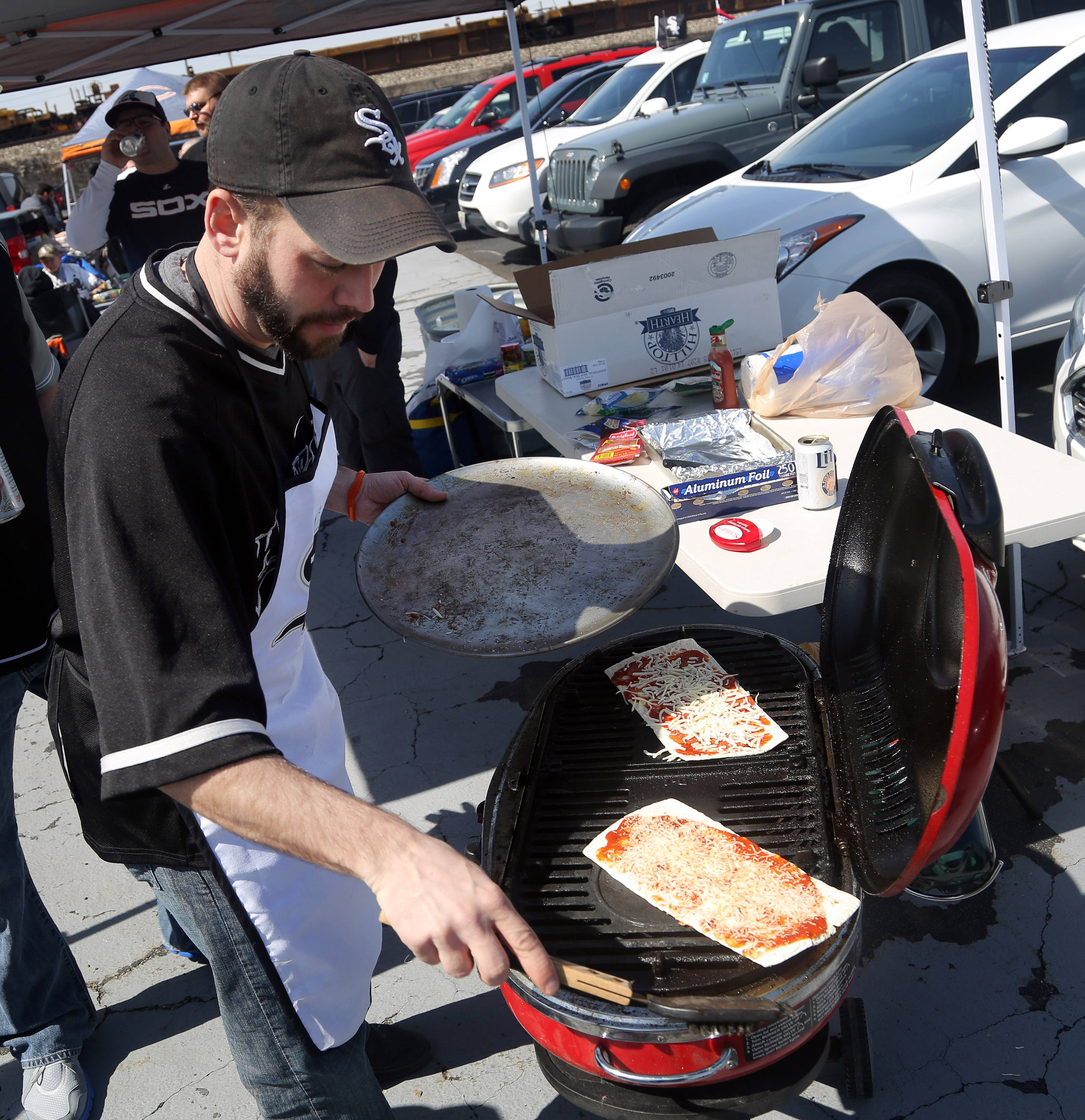 Mike Mele of Mundelein grills flatbread pizza Monday before the White Sox' first game of the season at U.S. Cellular Field.