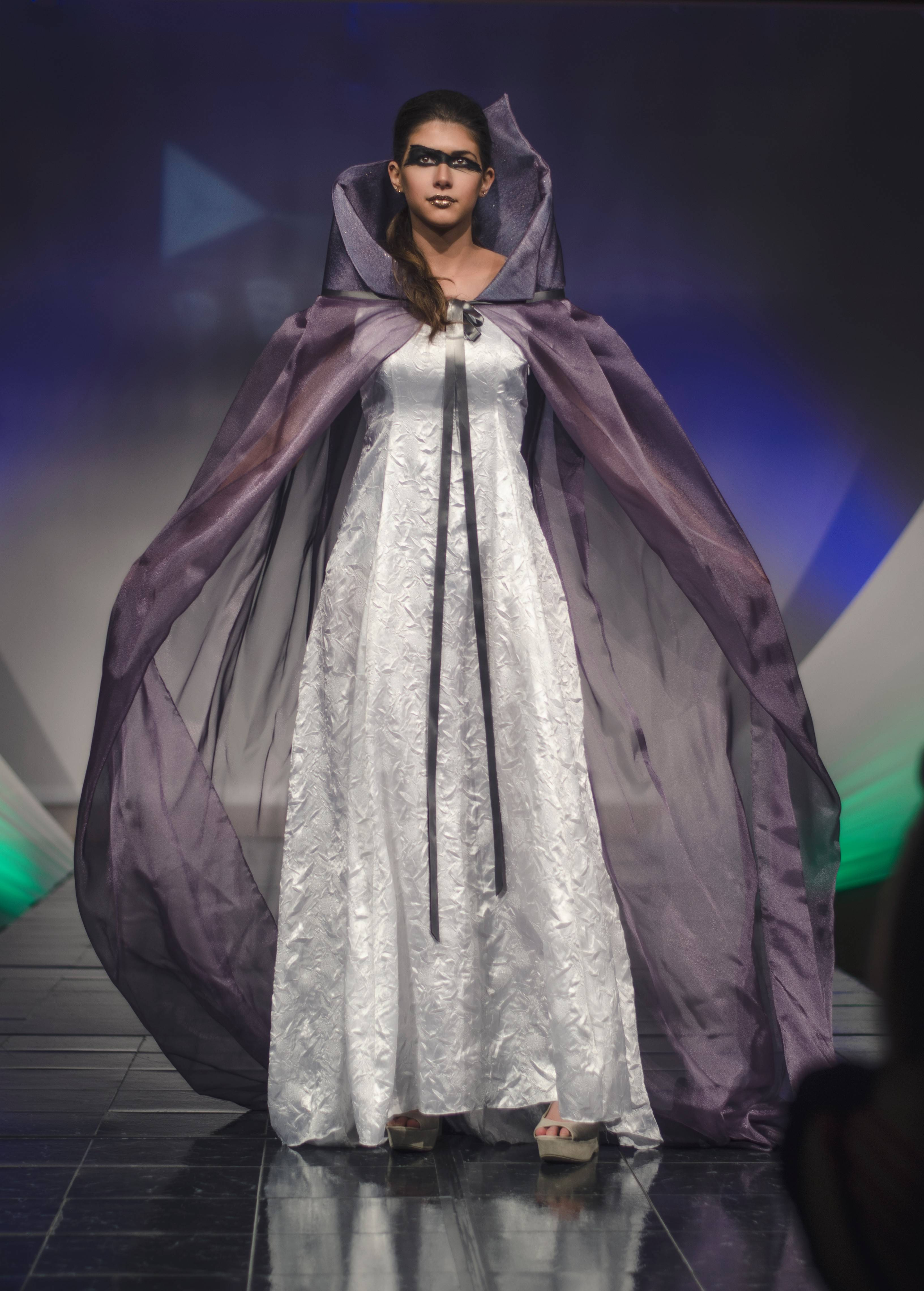 Mikayla Furlan is wearing a gown and cape by designer Ashley Alverth. The student-run fashion show raised more than $18,000 for Salute Inc. in Palatine.