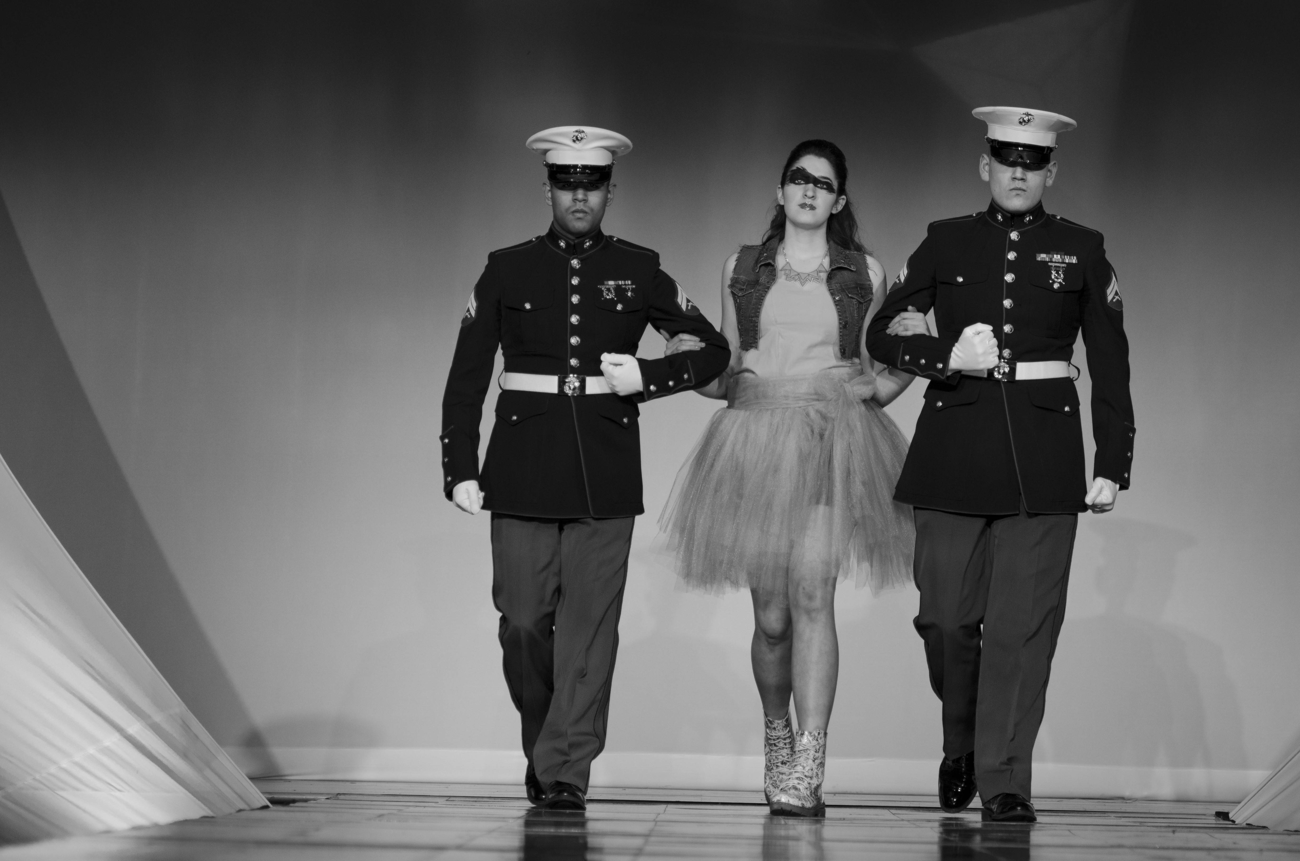 Joslyn De Norio, modeling her own design, is escorted by two Marines. The student-run fashion show raised more than $18,000 for Salute Inc. in Palatine, which helps veterans.