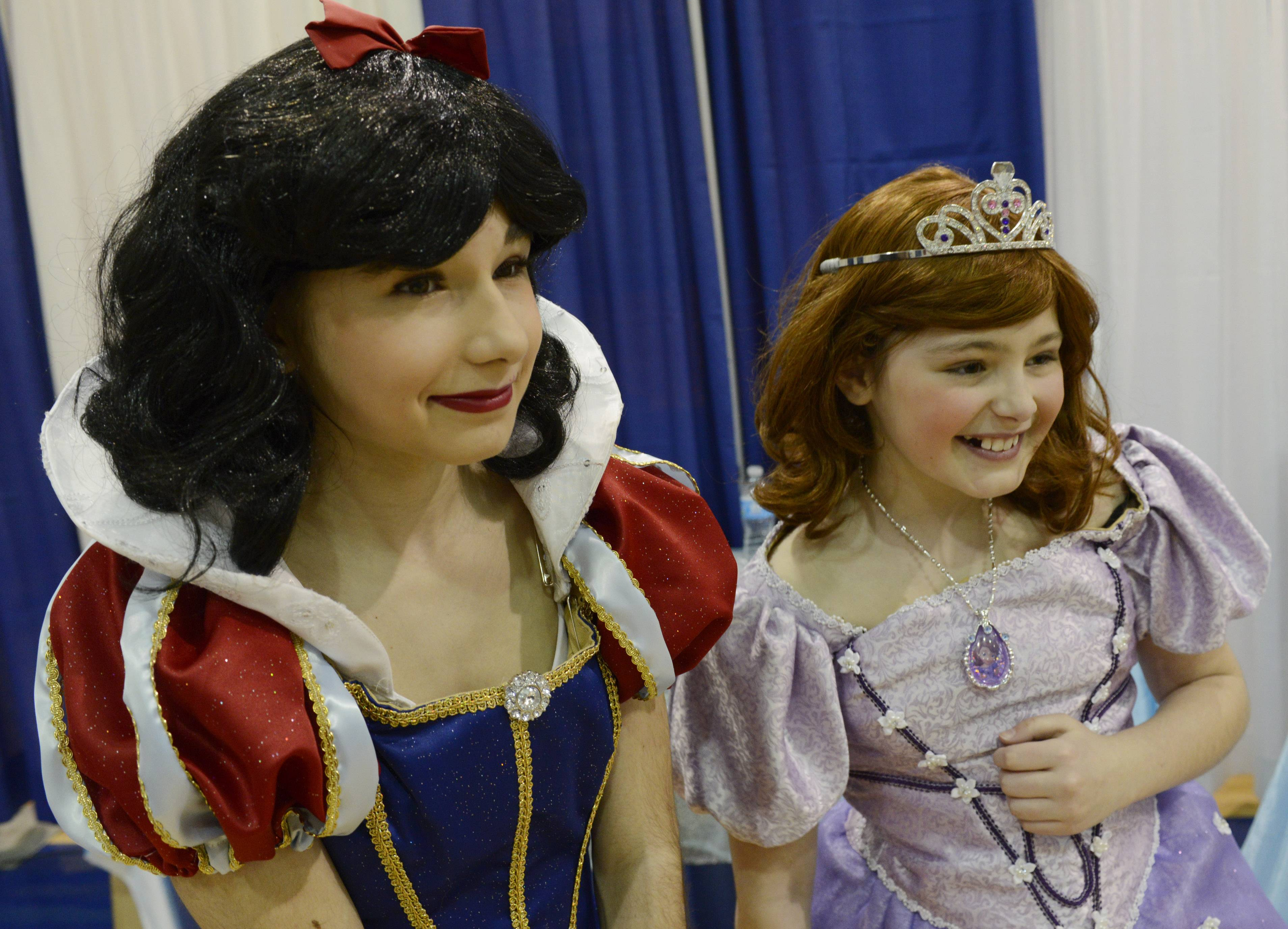 Lyndsey Bassett, 14, left, of Hainesville, is dressed as Snow White and her sister Lily, 10, is dressed as Princess Sofia, as they great visitors to the Round Lake Area Park District booth during the Springfest Expo 2014, held by the Lindenhurst-Lake Villa Chamber of Commerce at Lakes Community High School Saturday.
