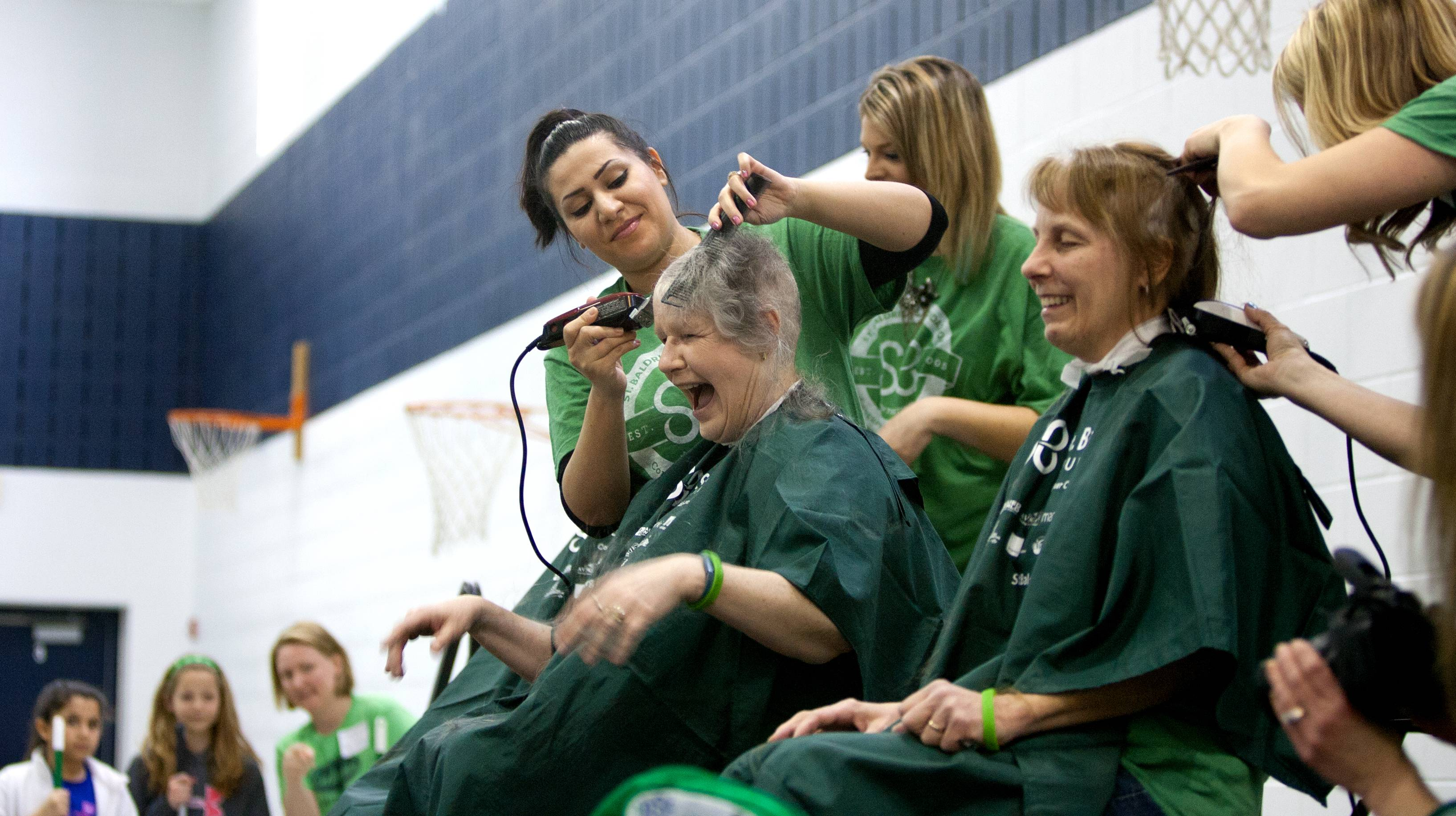 Educators Judy Bilitzki, left, and Pam Menzel, right, receive their haircuts, as students and staff at Madison School in Wheaton participate in a fundraiser for the St. Baldrick's foundation.