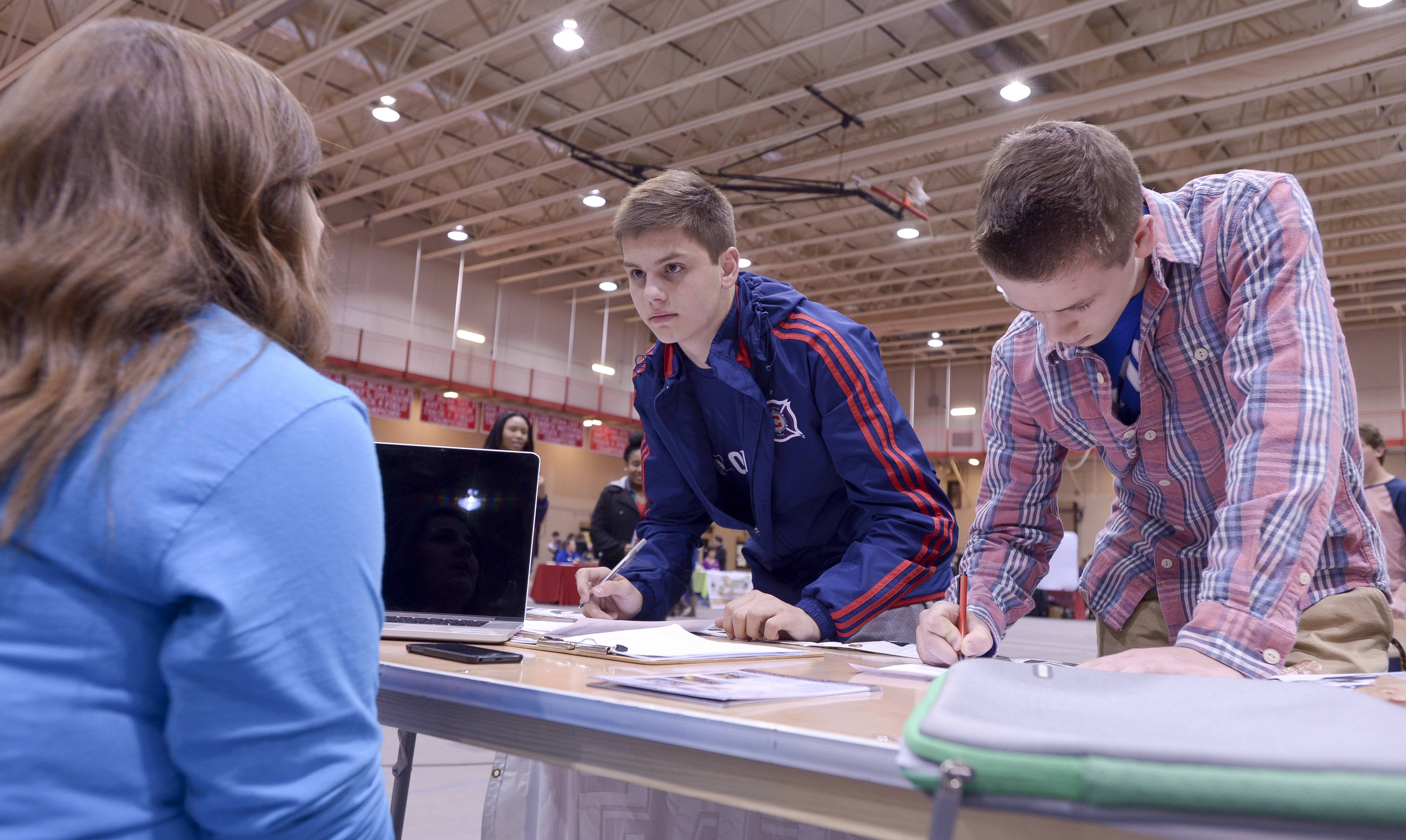 Becca Dolak, from Players Indoor Sports Center, talks with David Kovacevic, 16, of Naperville, and Breigs Pflibsen, 16, of Aurora, as they fill out applications during the 11th annual KidsMatter Student Job Fair at North Central College in Naperville. The job fair had 45 vendors.