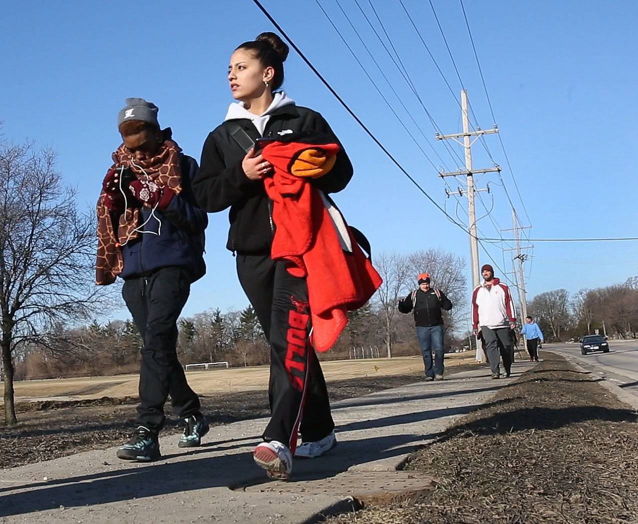 Sara Franklin, left and Janice Sanchez, right, seniors from East Aurora High School, make their way down Chicago Avenue in Lisle on Wednesday with other classmates, as they walk 38 miles to Soldier Field in Chicago. They are raising money to bring a former child soldier from Sierre Leone to speak at their school in April.