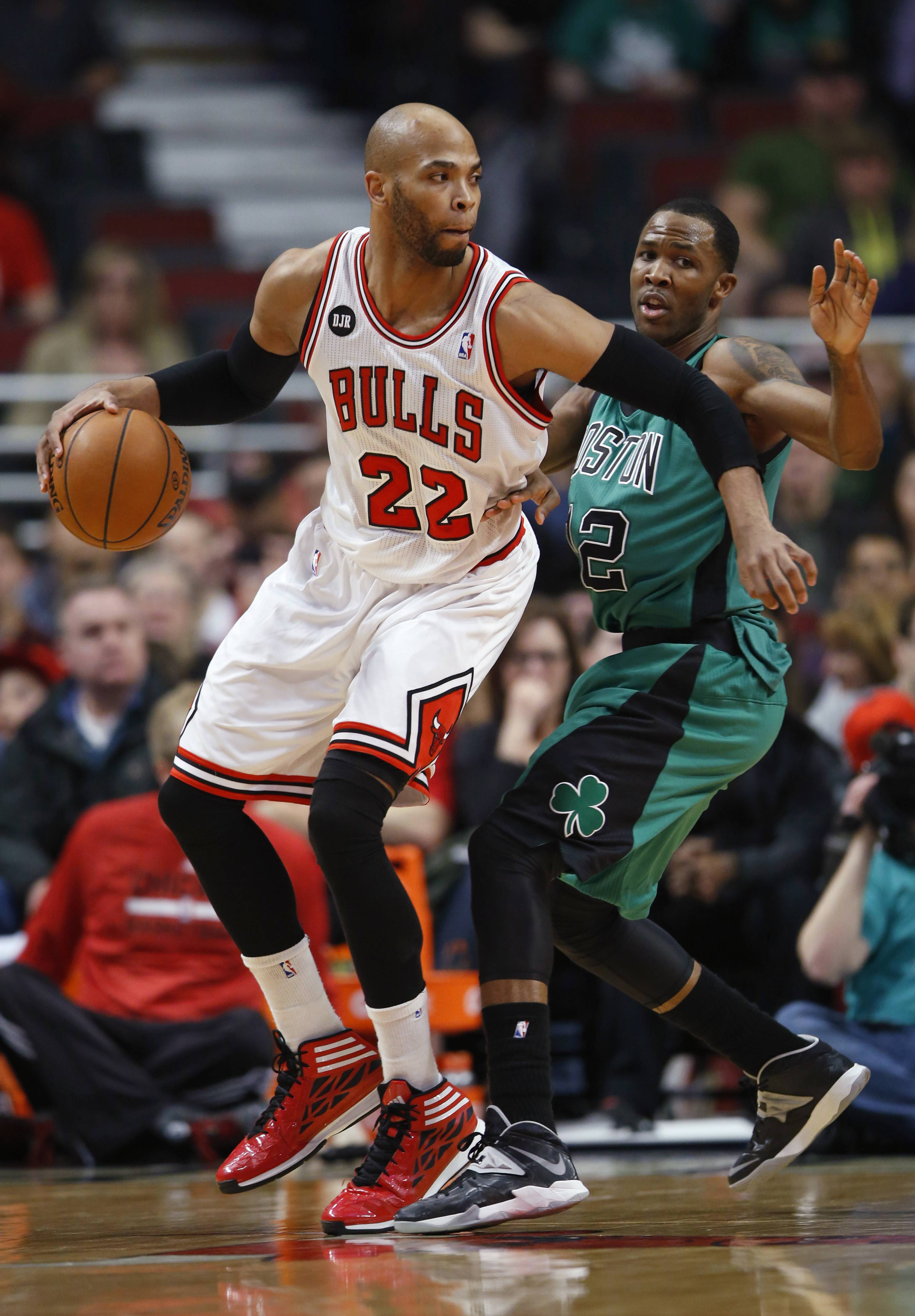 Bulls forward Taj Gibson, left, looks to pass the ball against Boston Celtics forward Chris Johnson, right, during the first half of an NBA basketball game in Chicago, Monday, March 31, 2014.