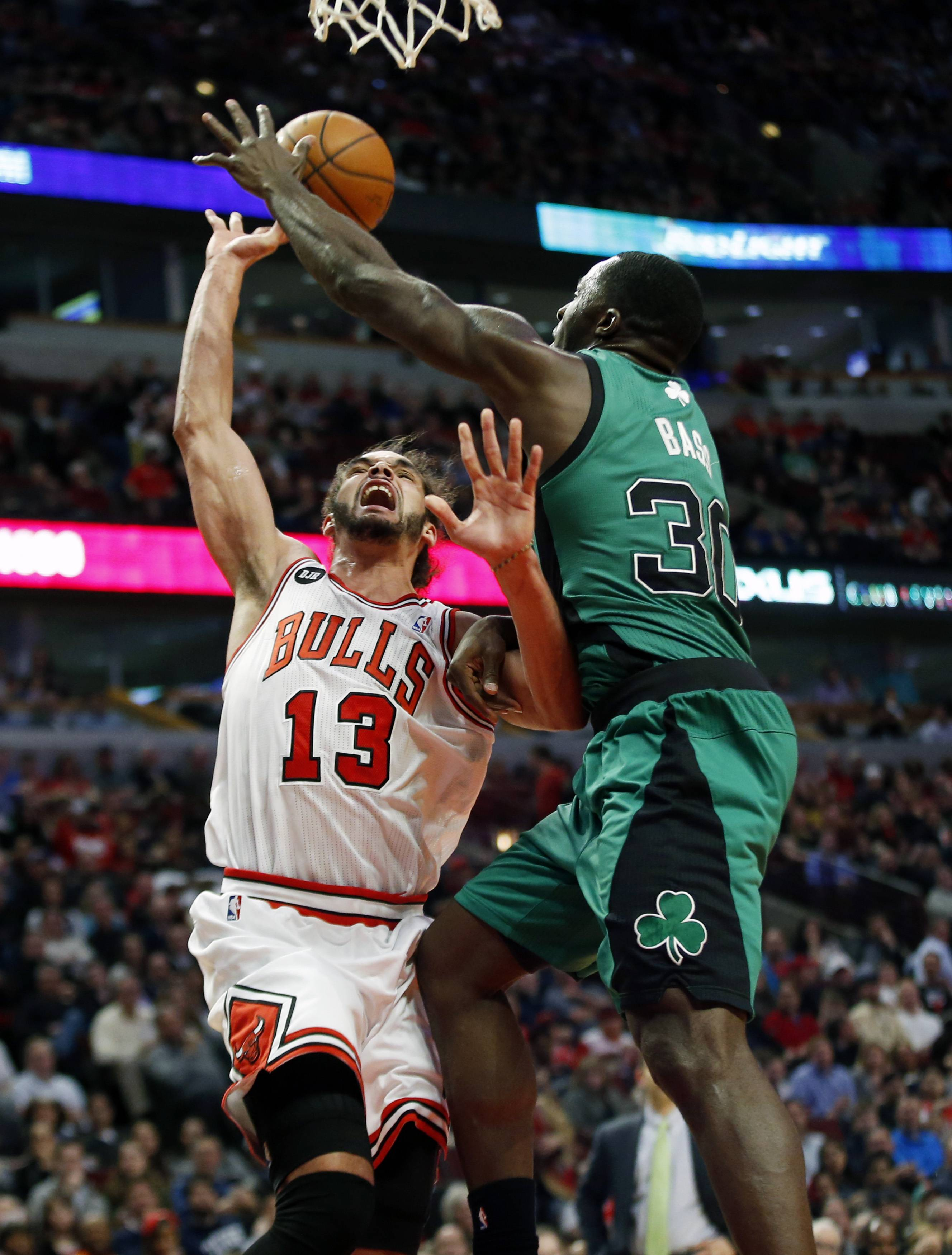 Chicago Bulls center Joakim Noah, left, is fouled on the way to the basket by Boston Celtics forward Brandon Bass, right, during the second half of an NBA basketball game in Chicago, Monday, March 31, 2014. The Bulls won 94-80.