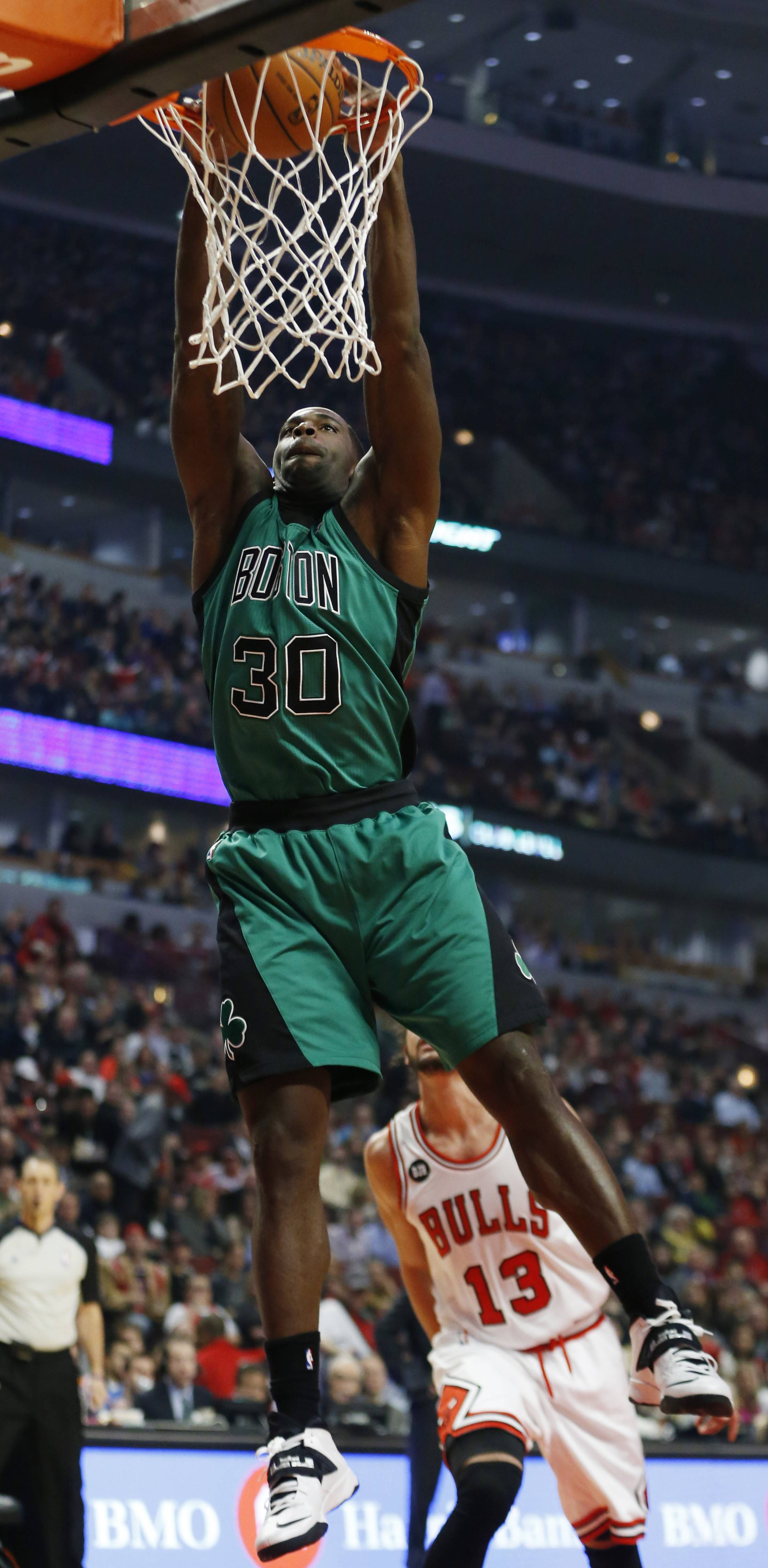 Boston Celtics forward Brandon Bass dunks against the Chicago Bulls during the first half of an NBA basketball game in Chicago, Monday, March 31, 2014.