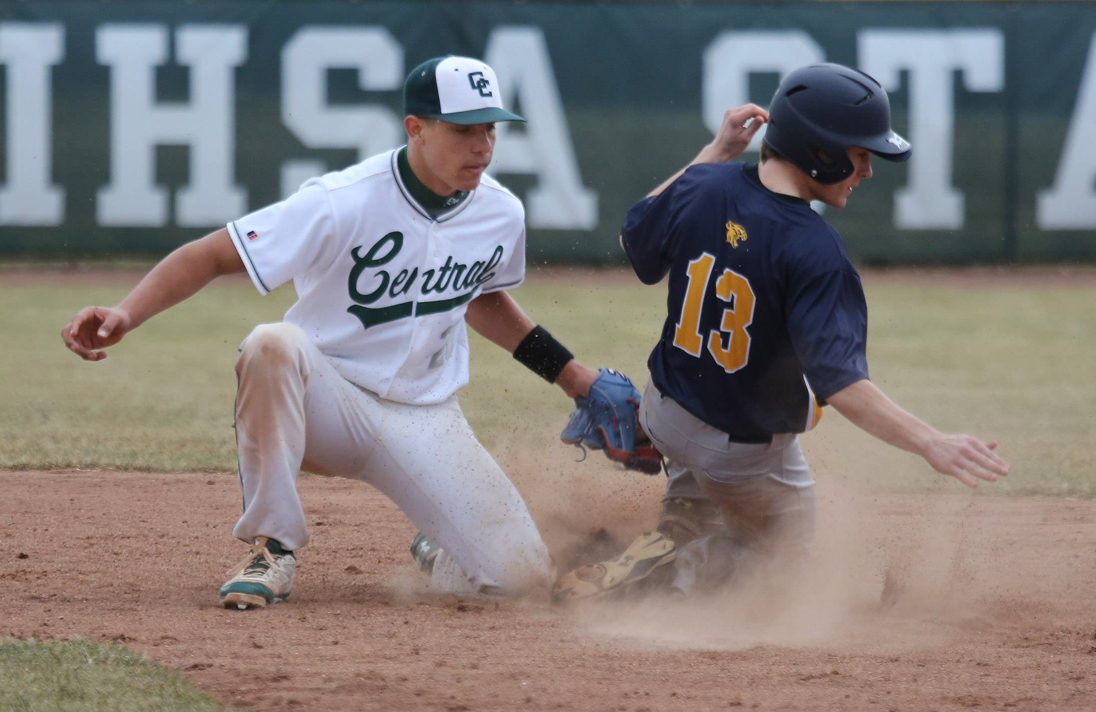 Round Lake runner Ryan Newman slides safely into second base, beating the tag of second baseman Freddie Landers in the third inning Monday at Grayslake Central.