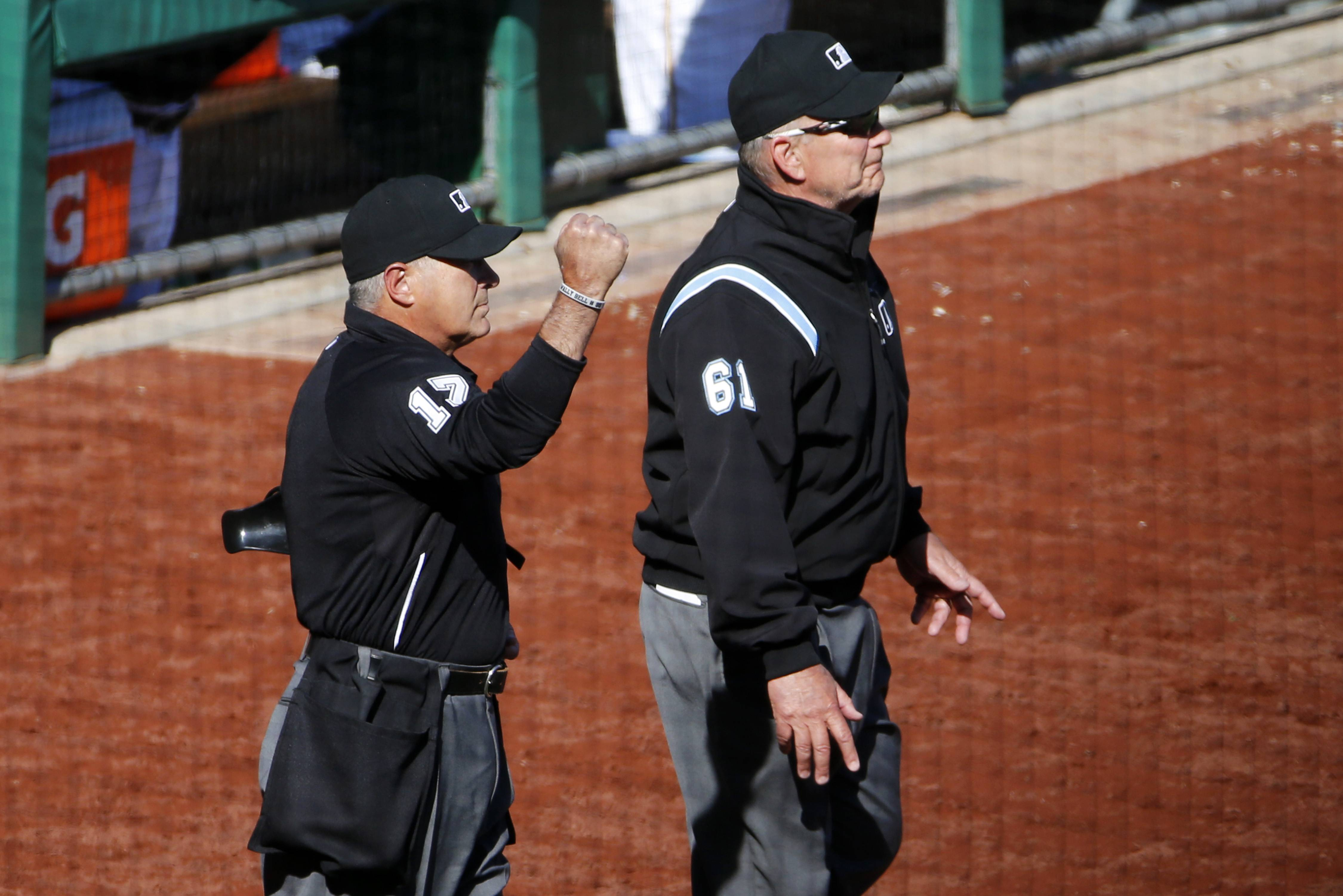Home plate umpire John Hirschbeck, left, makes the out call at first base after he and first base umpire Bob Davidson (61) were asked by the Pirates for a review of a pickoff safe call at first base in the 10th inning Monday.