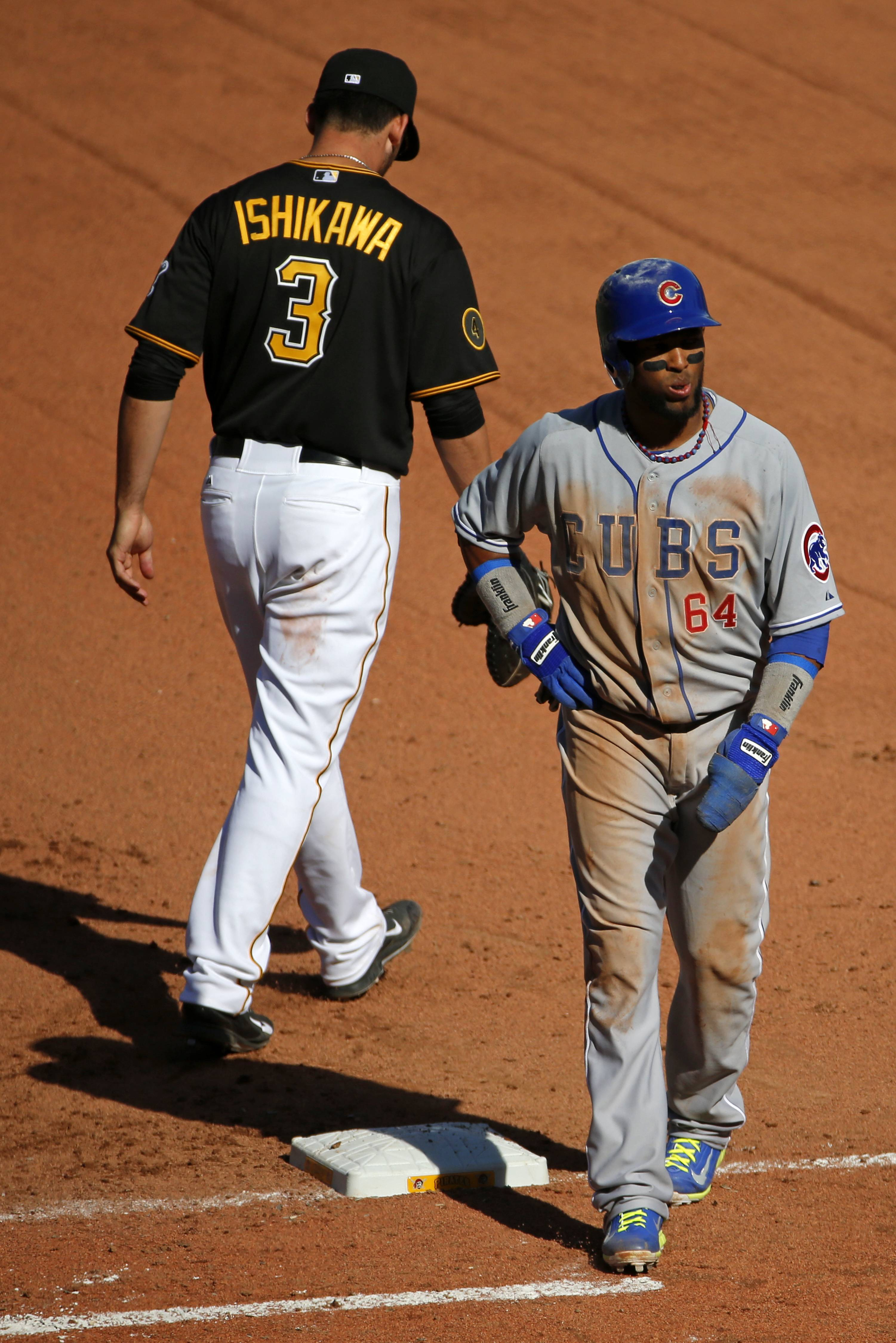 The Cubs' Emilio Bonifacio walks off first base after being ruled out by home plate umpire John Hirschbeck as the result of review requested by Pittsburgh Pirates manager Clint Hurdle.