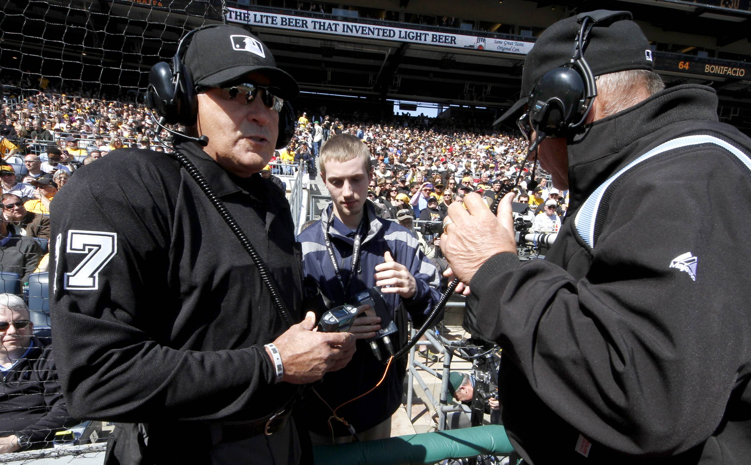 First base umpire Bob Davidson, right, and home plate umpire John Hirschbeck, left, talk over headsets as a play at first base is being reviewed in the fifth inning. Chicago Cubs manager Rick Renteria requested a replay on an out call.