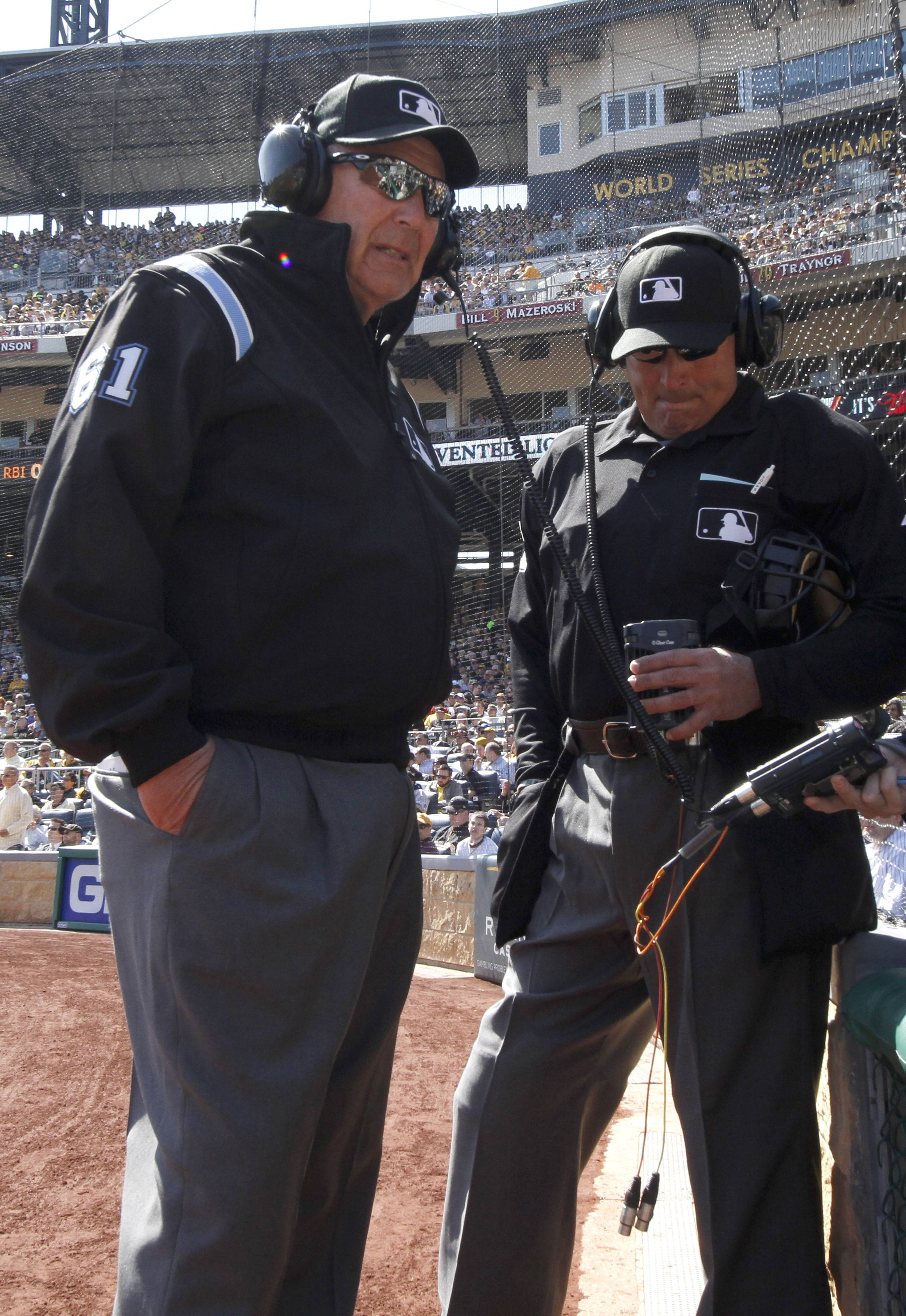First base umpire Bob Davidson and home plate umpire John Hirschbeck, talk over headsets as a play at first base is being reviewed in the fifth inning. Chicago Cubs manager Rick Renteria requested a replay on an out call.