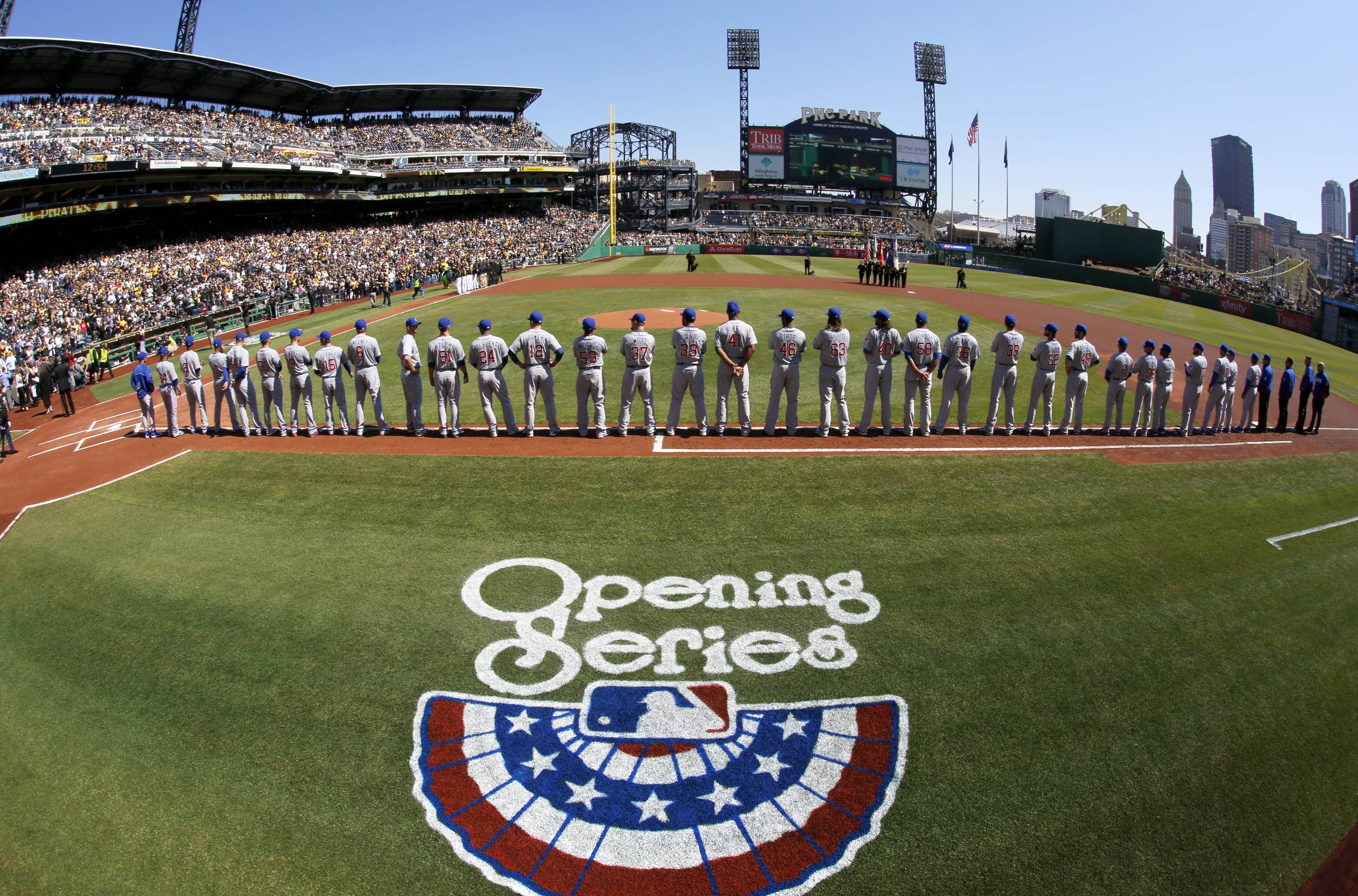 The Chicago Cubs line up along the first base line during opening day ceremonies .