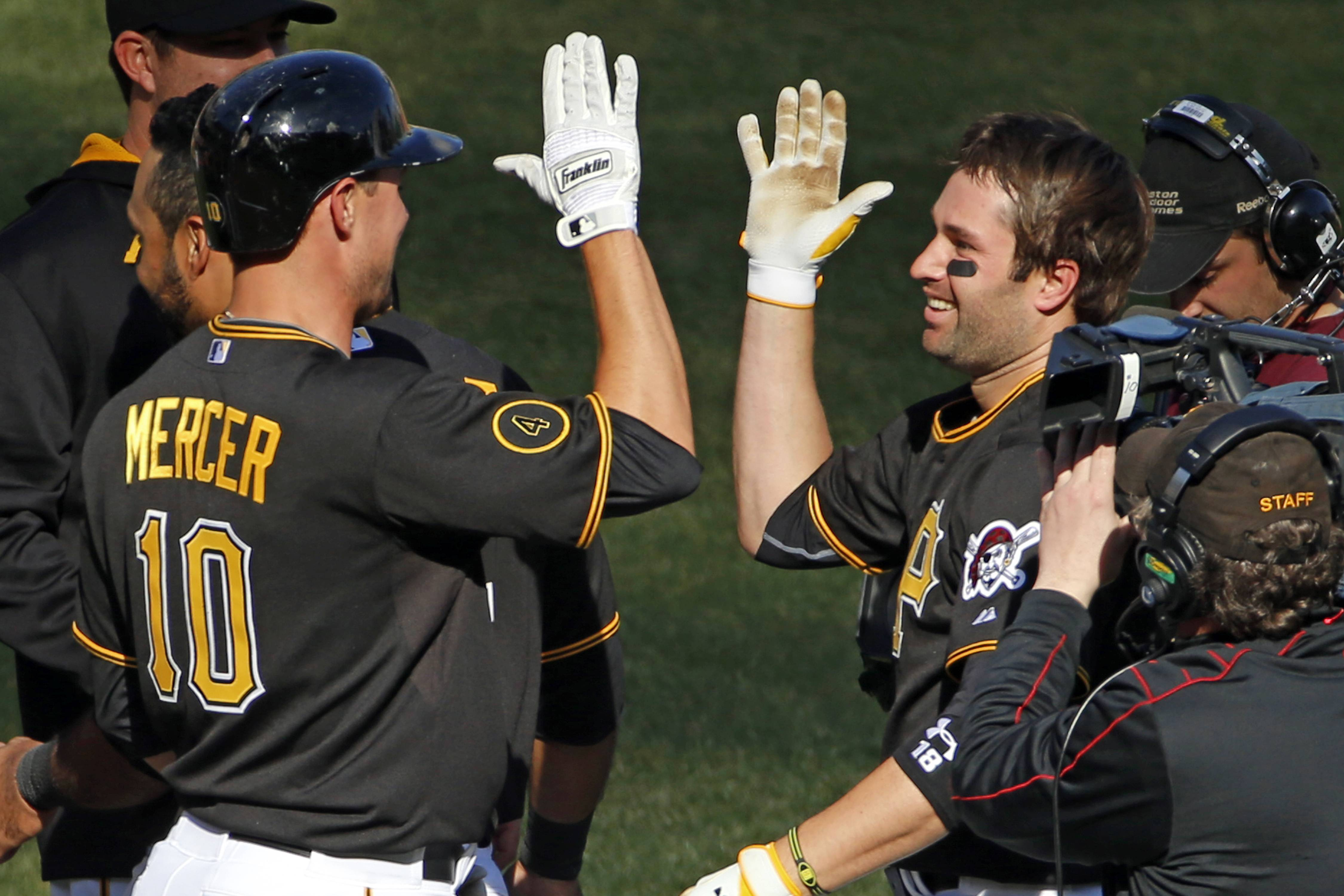 Pittsburgh Pirates' Neil Walker, right, celebrates with teammate Jordy Mercer (10) after hitting a walk-off solo-home run off Chicago Cubs relief pitcher Carlos Villanueva.