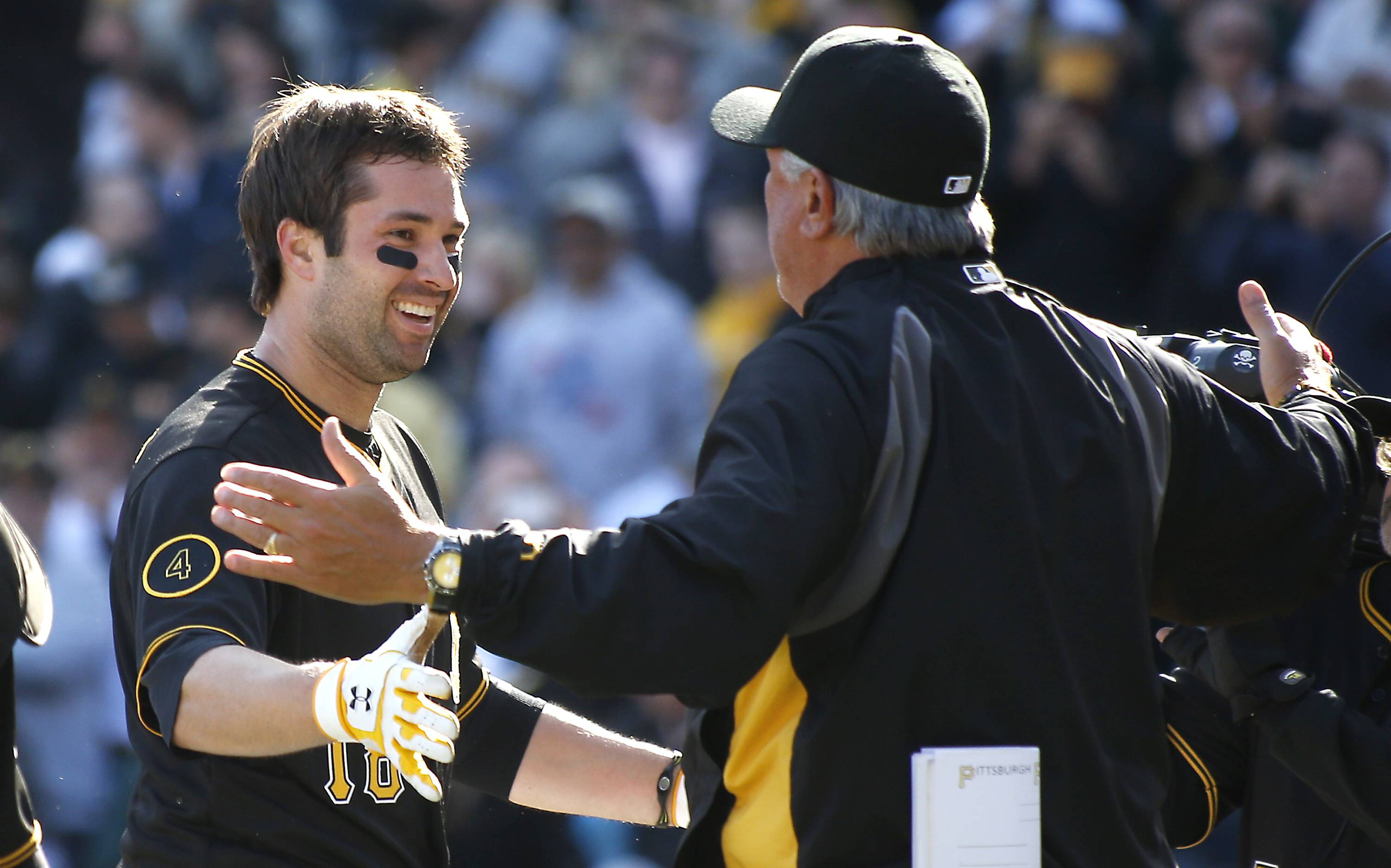 Pittsburgh Pirates' Neil Walker, left, is greeted by manager Clint Hurdle after hitting the game winning home run in the tenth inning .