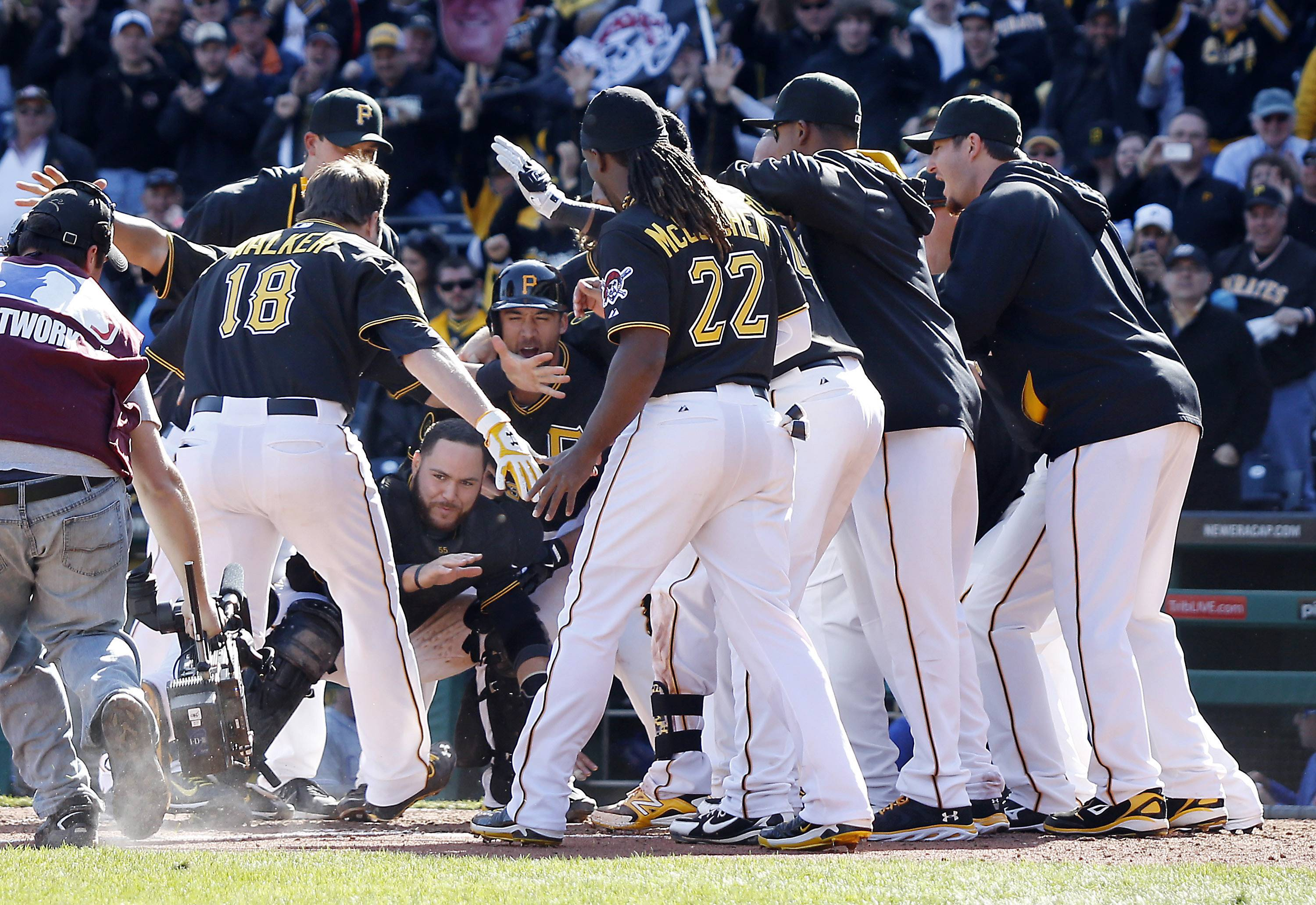 The Pittsburgh Pirates circle home plate as they wait for Neil Walker (18) to tag the plate after he hit a game-winning home run in the tenth inning.