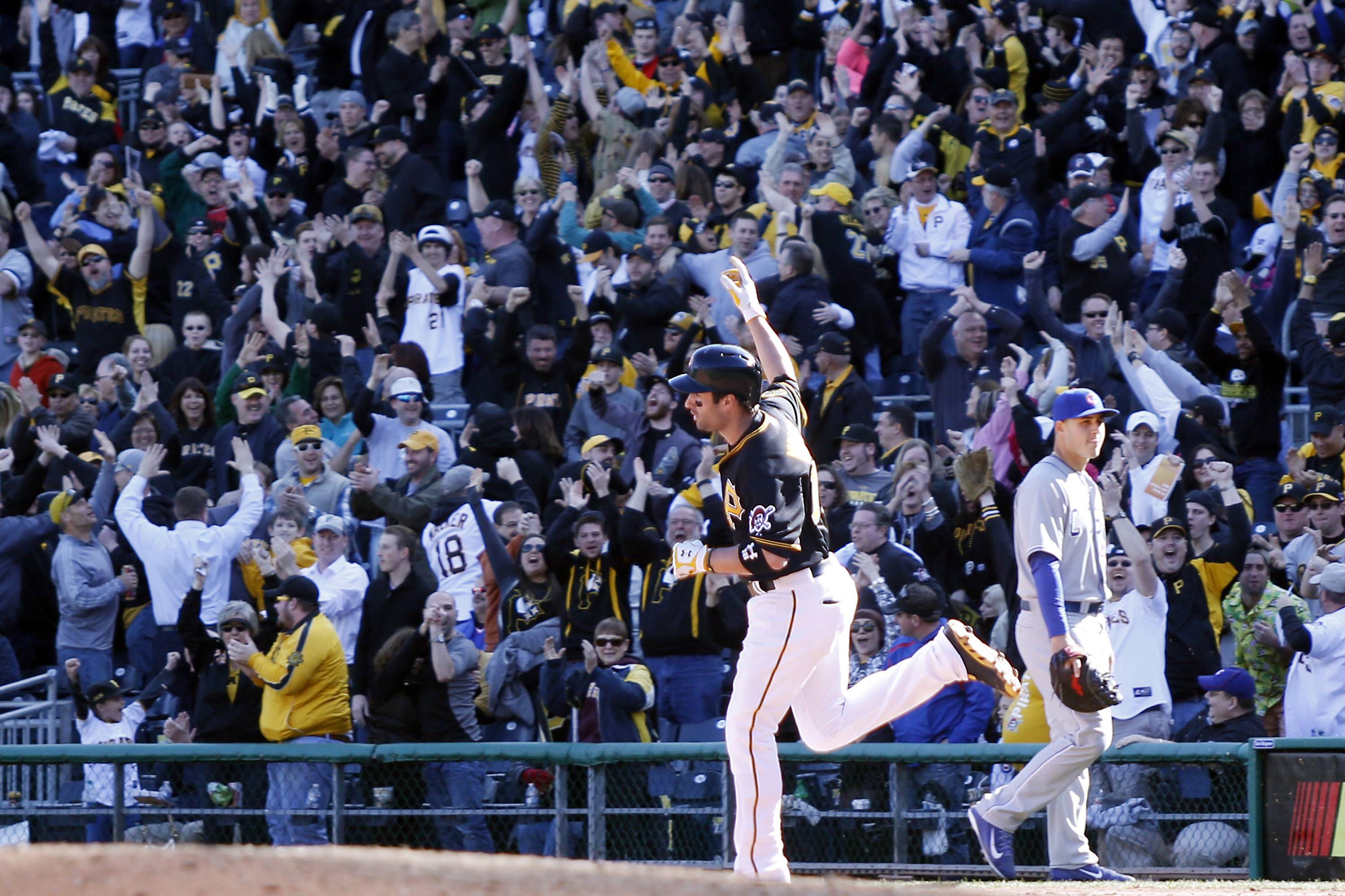 Fans cheer as Pittsburgh Pirates' Neil Walker (18) pumps his fist as he rounds the bases after hitting the game-winning home run while Chicago Cubs first baseman Anthony Rizzo, right, walks off the field in the tenth inning.