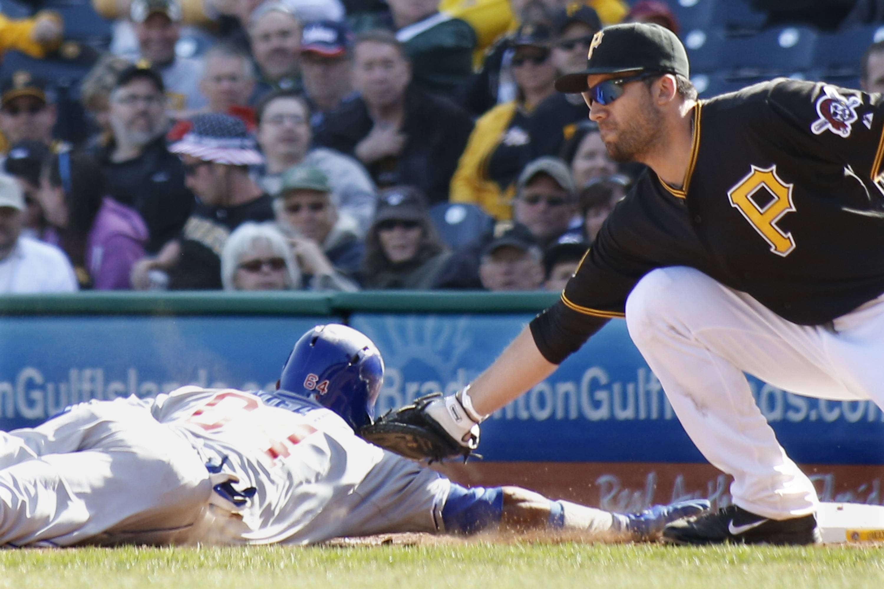 Pittsburgh Pirates first baseman Travis Ishikawa, right, reaches to tag Chicago Cubs Emilio Bonifacio as he dives back to first on a pickoff attempt in the tenth inning the opening day baseball game on Monday, March 31, 2014, in Pittsburgh. The Pirates won 1-0 in ten innings. Bonifacio was initially called safe by the first base umpire, but the call was overturned on a review requested by manager Clint Hurdle and Bonifacio was ruled out.