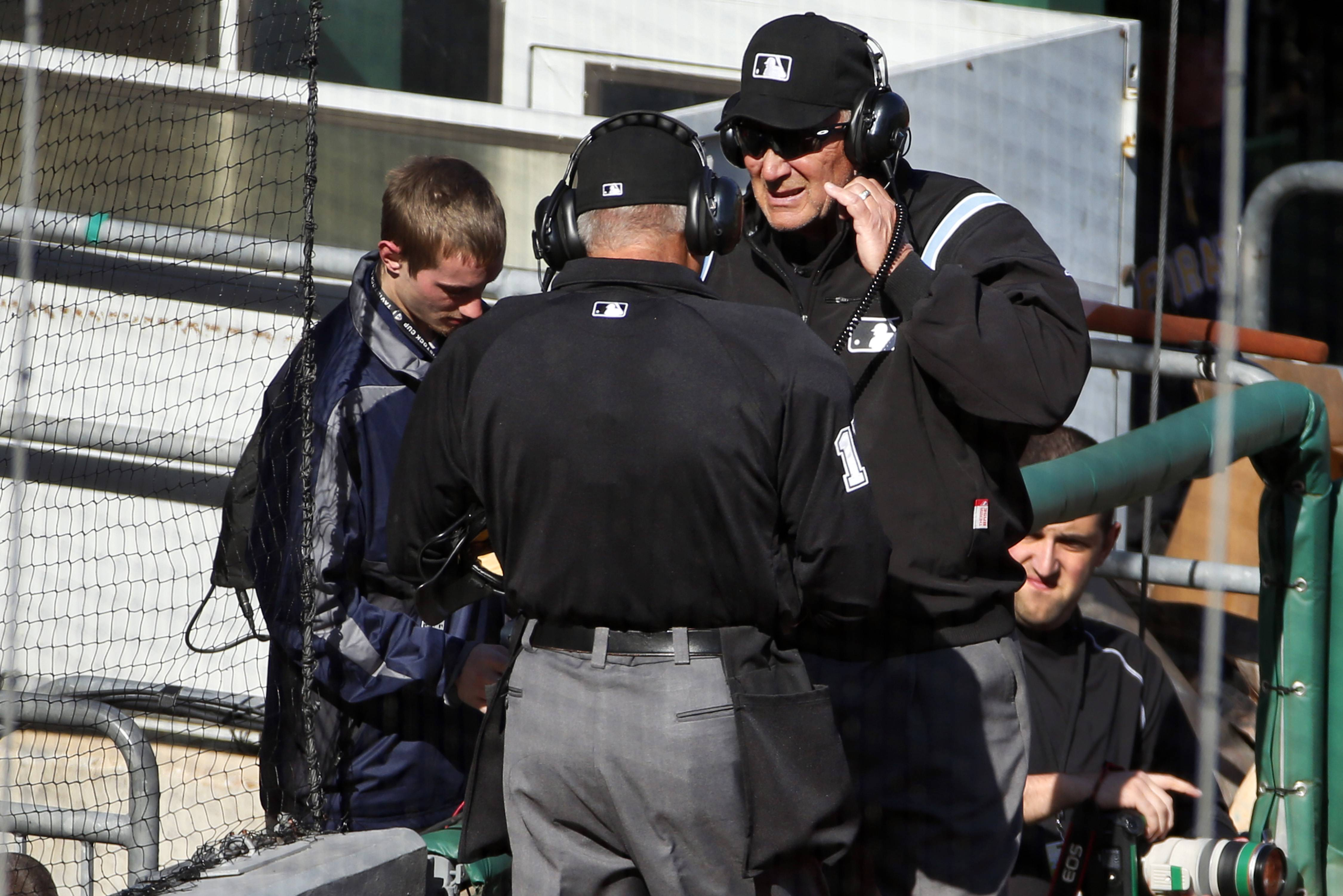 First base umpire Bob Davidson, right, and home plate umpire John Hirschbeck talk over headsets as a pickoff safe call at first base is reviewed in the tenth inning.