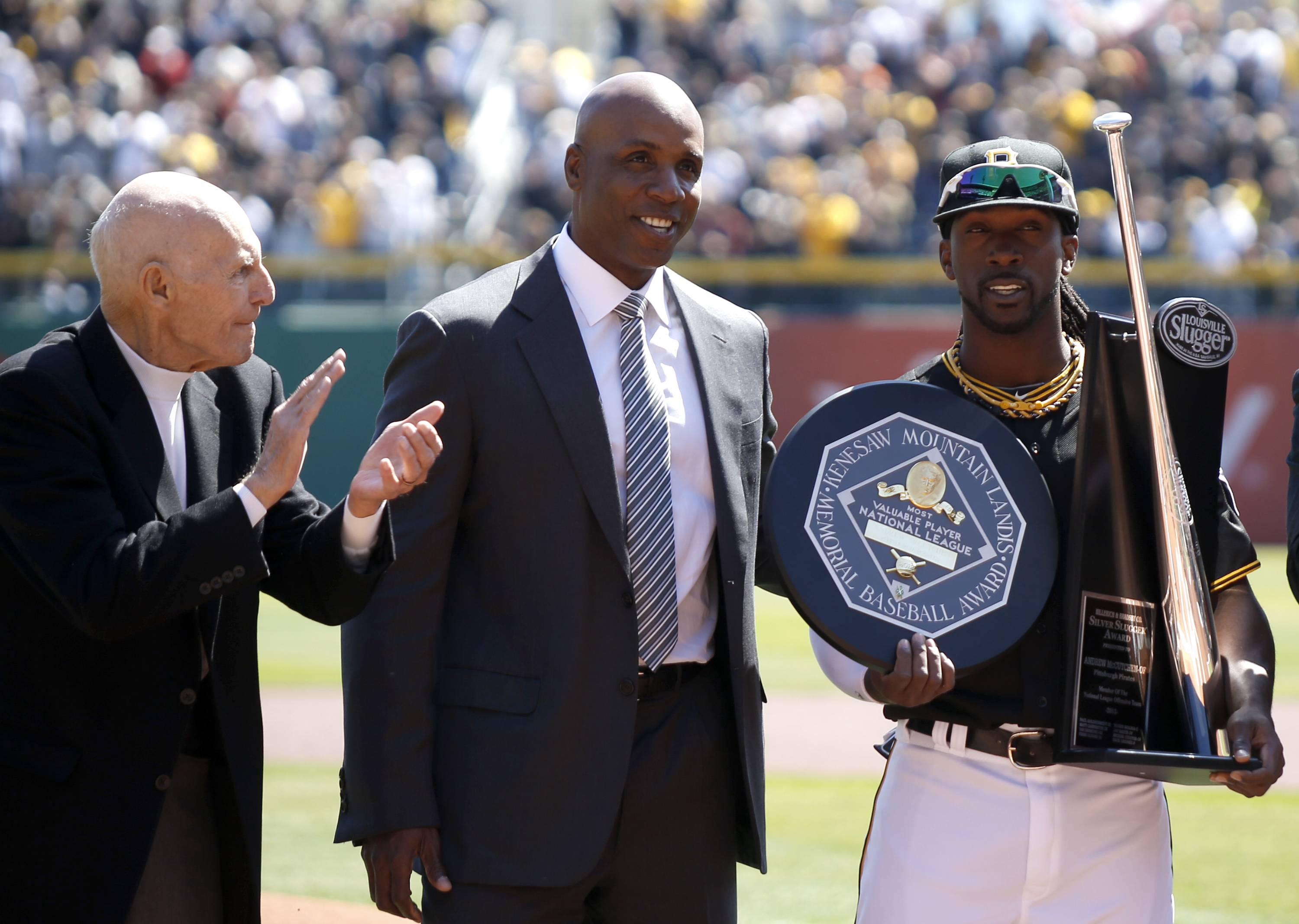Pittsburgh Pirates center fielder Andrew McCutchen, right, holds his NL MVP trophy and his Silver Slugger award as he poses with former Pittsburgh Pirates outfielder Barry Bonds, center, and former Pittsburgh Pirates shortstop Dick Groat, both former NL baseball MVP award winners.