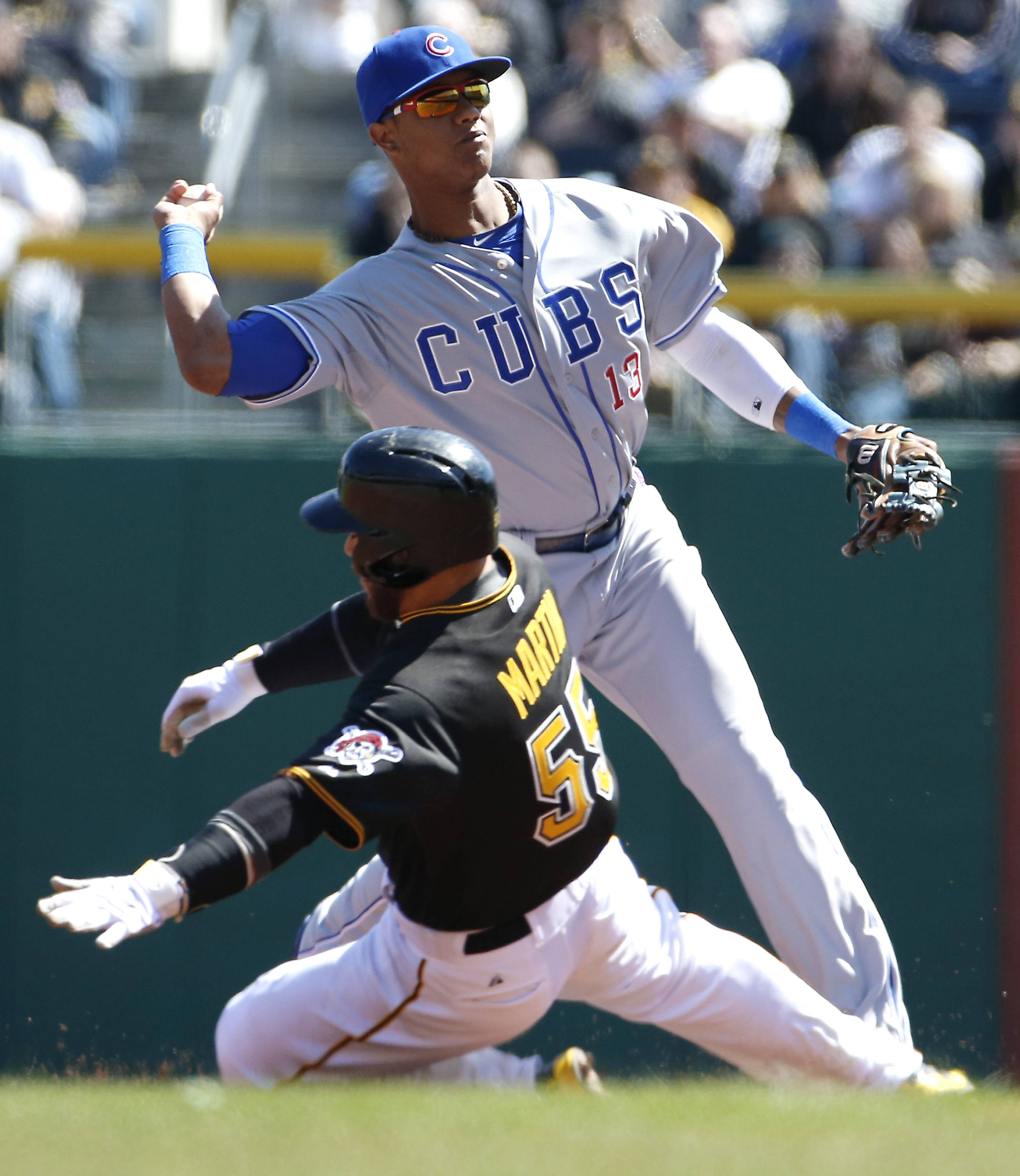 Chicago Cubs' Starlin Castro throws to first to complete a double play on Pittsburgh Pirates' Neil Walker as Russell Martin  slides into second .
