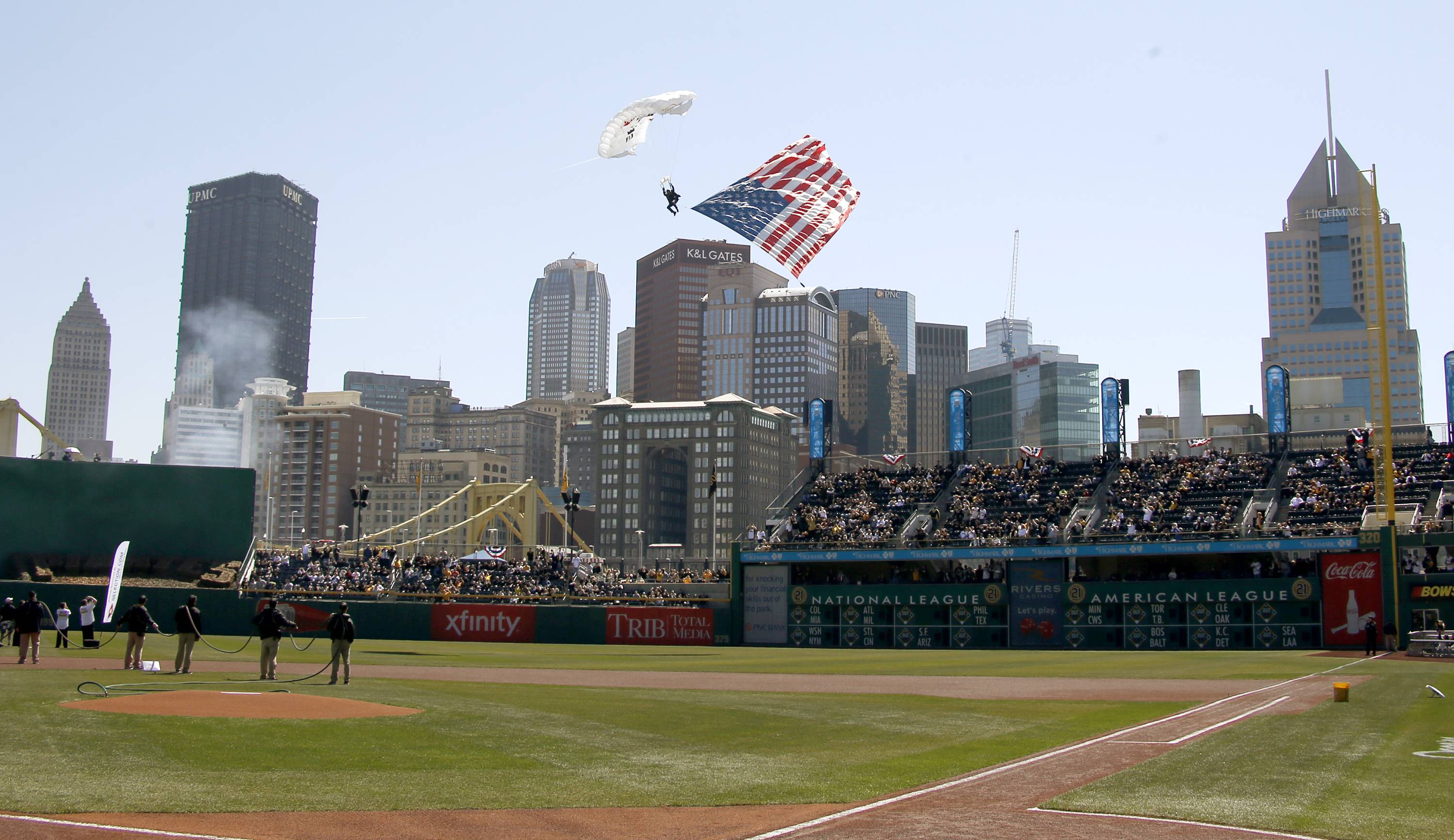 A paratrooper with an American flag descends onto PNC Park during opening day ceremonies.