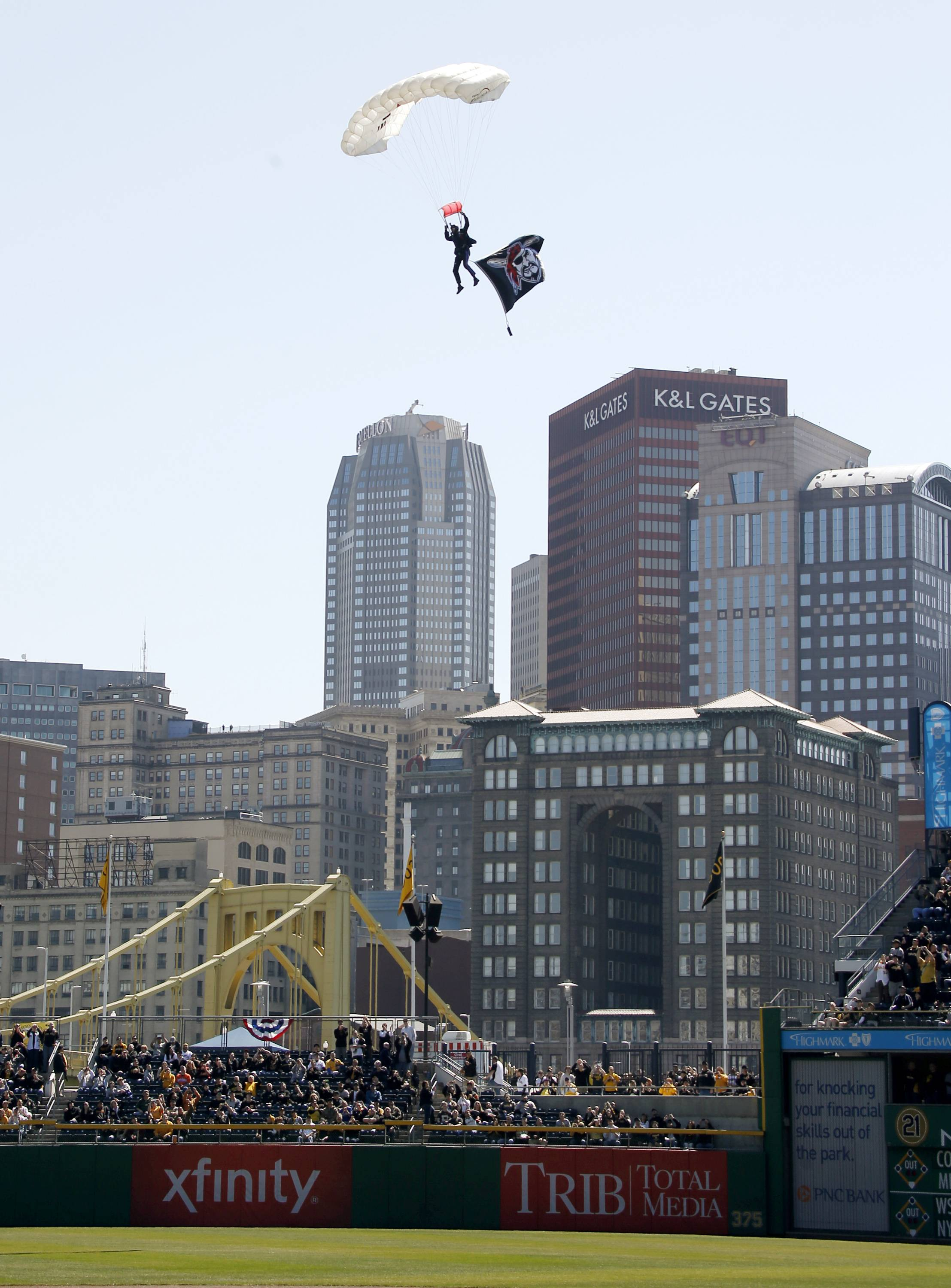 A paratrooper with a flag descends over the Pittsburgh skyline onto PNC Park during opening day ceremonies.